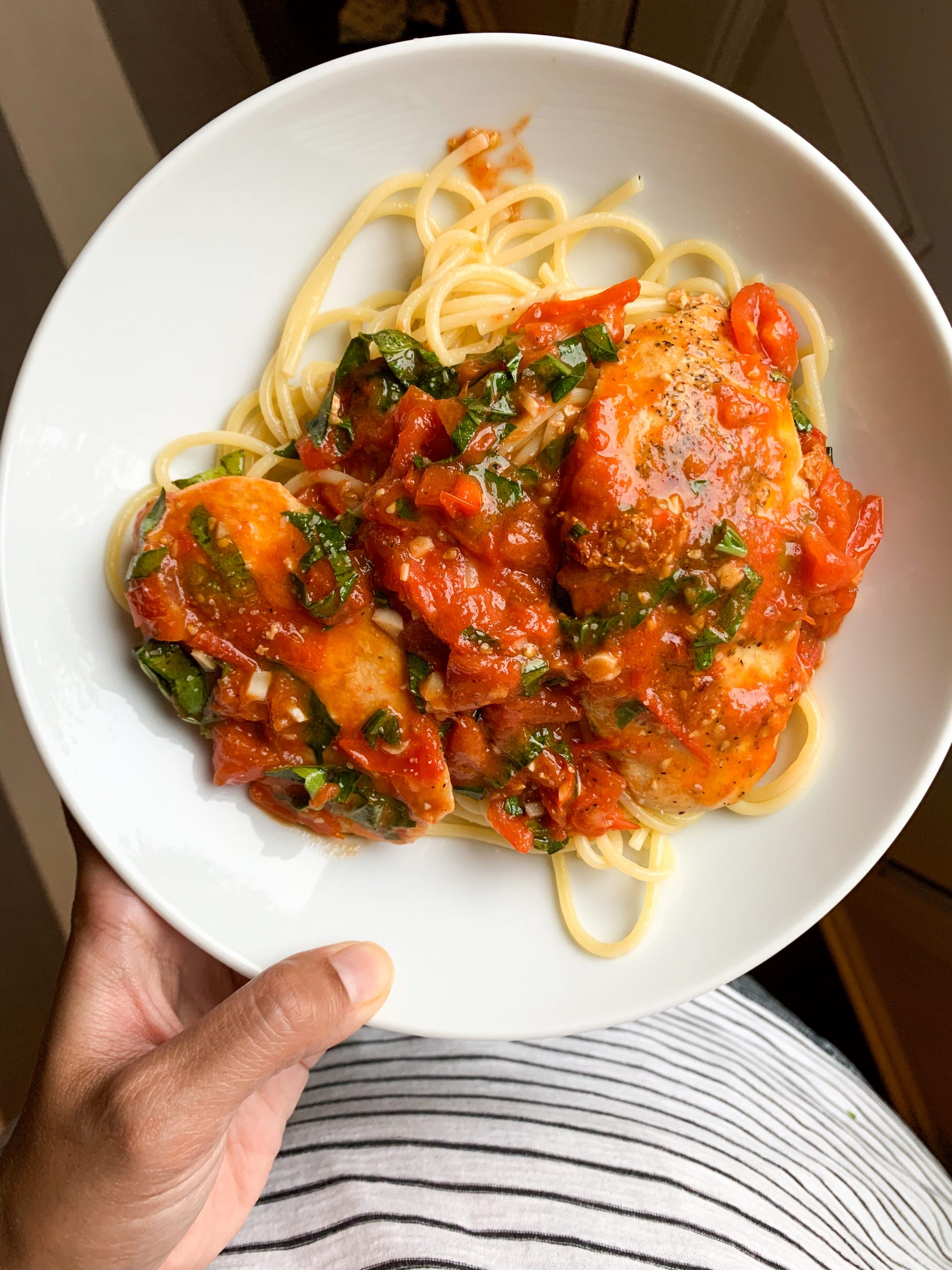 plate with spaghetti toped with tomato basil sauce and small chicken pieces