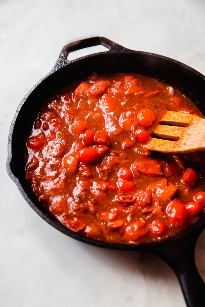 prepared sauce in cast iron skillet with wooden spoon