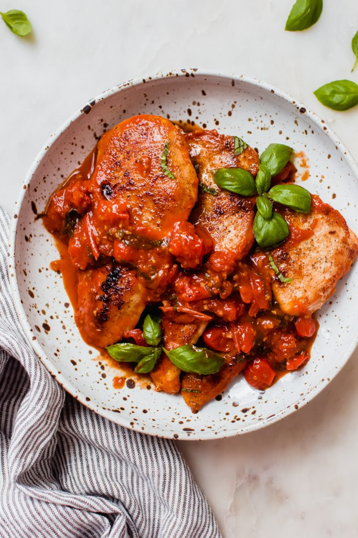 speckled plate holding three browed chicken filets with sprigs of fresh basil in tomato basil sauce