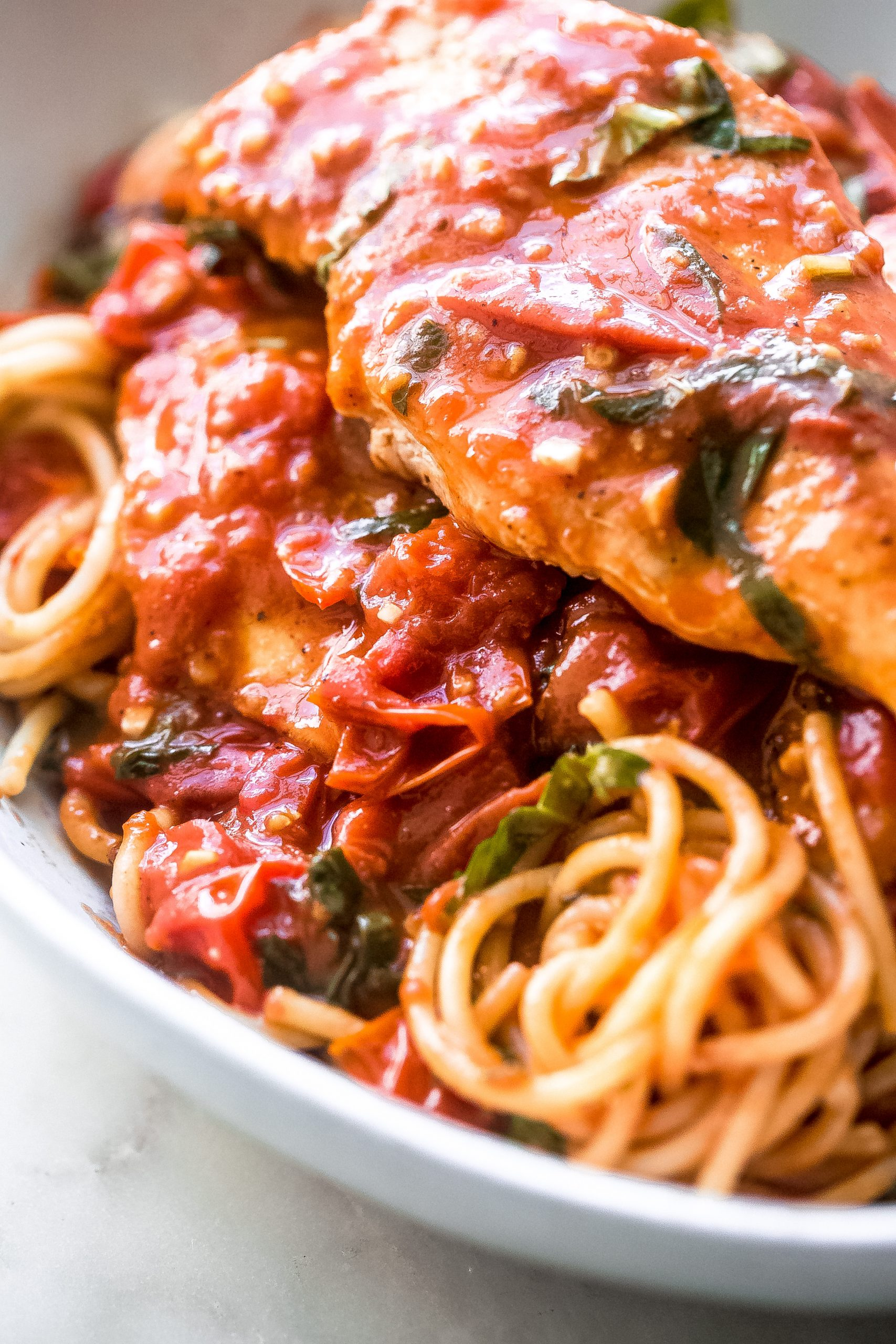 close up of spaghetti topped with tomato basil sauce and seared chicken