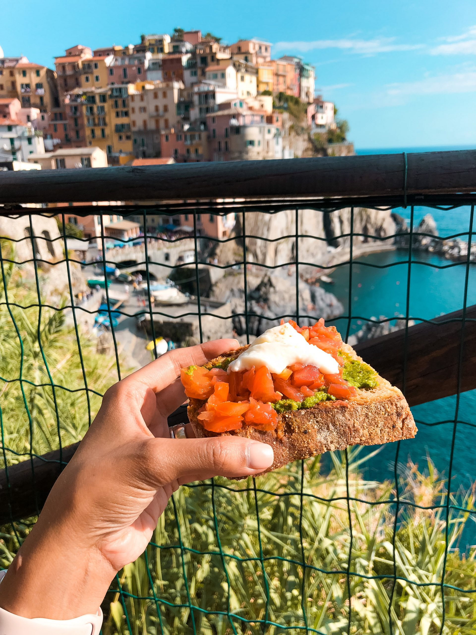 tomatoes, pesto, and ricotta on bread with Vernazza coastline in the backdrop