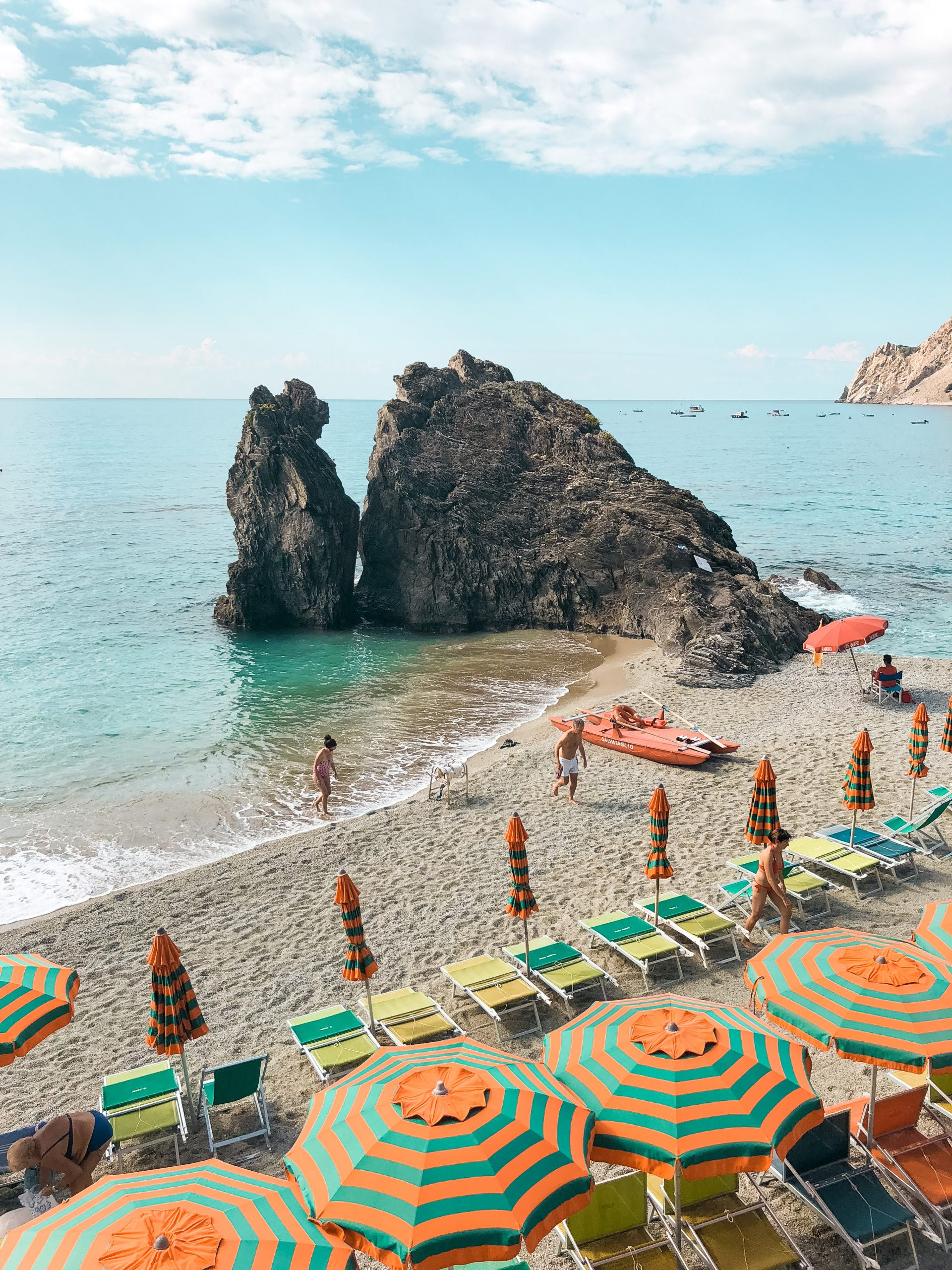 the beach at Monterosso al Mar with orange and teal umbrellas all along the beachside