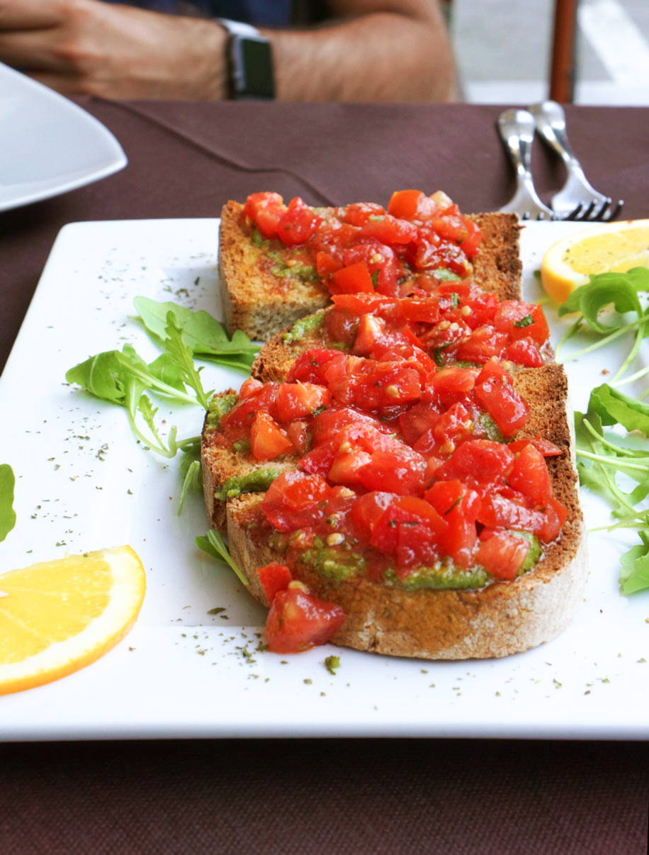 close up of toasted bread, topped with pesto and chopped tomatoes on a white plate