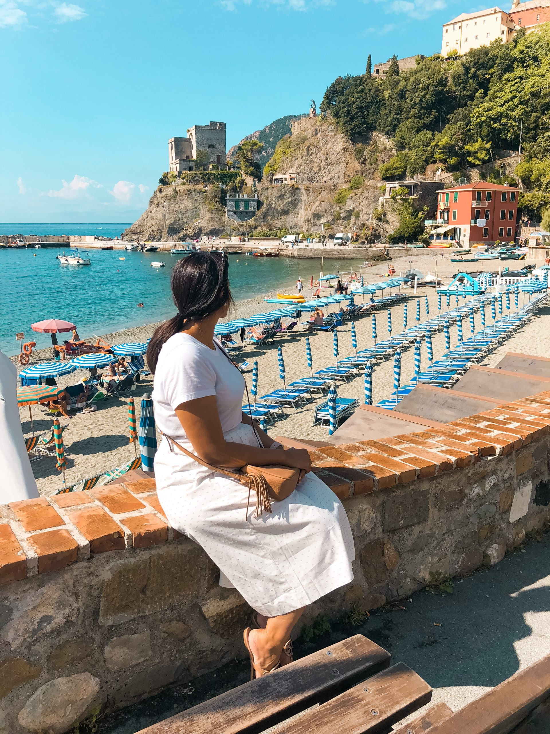me sitting on a brick wall with the beach at Monterosso al Mar behind me