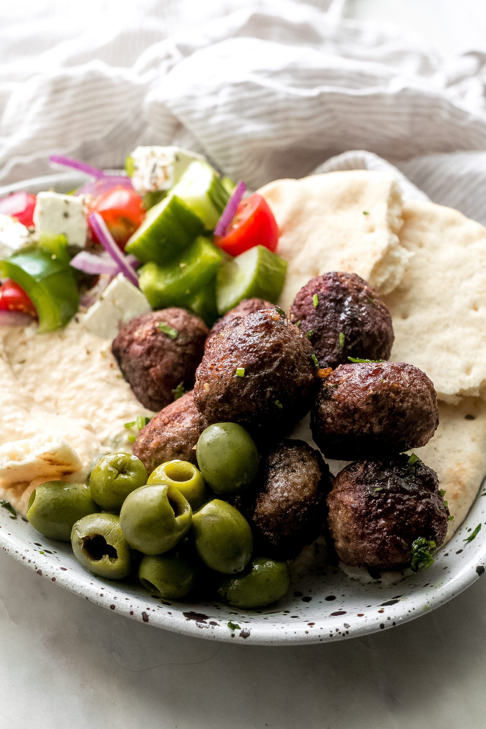 Greek Meatballs on speckled plate with hummus, bread, olives, and Greek Salad