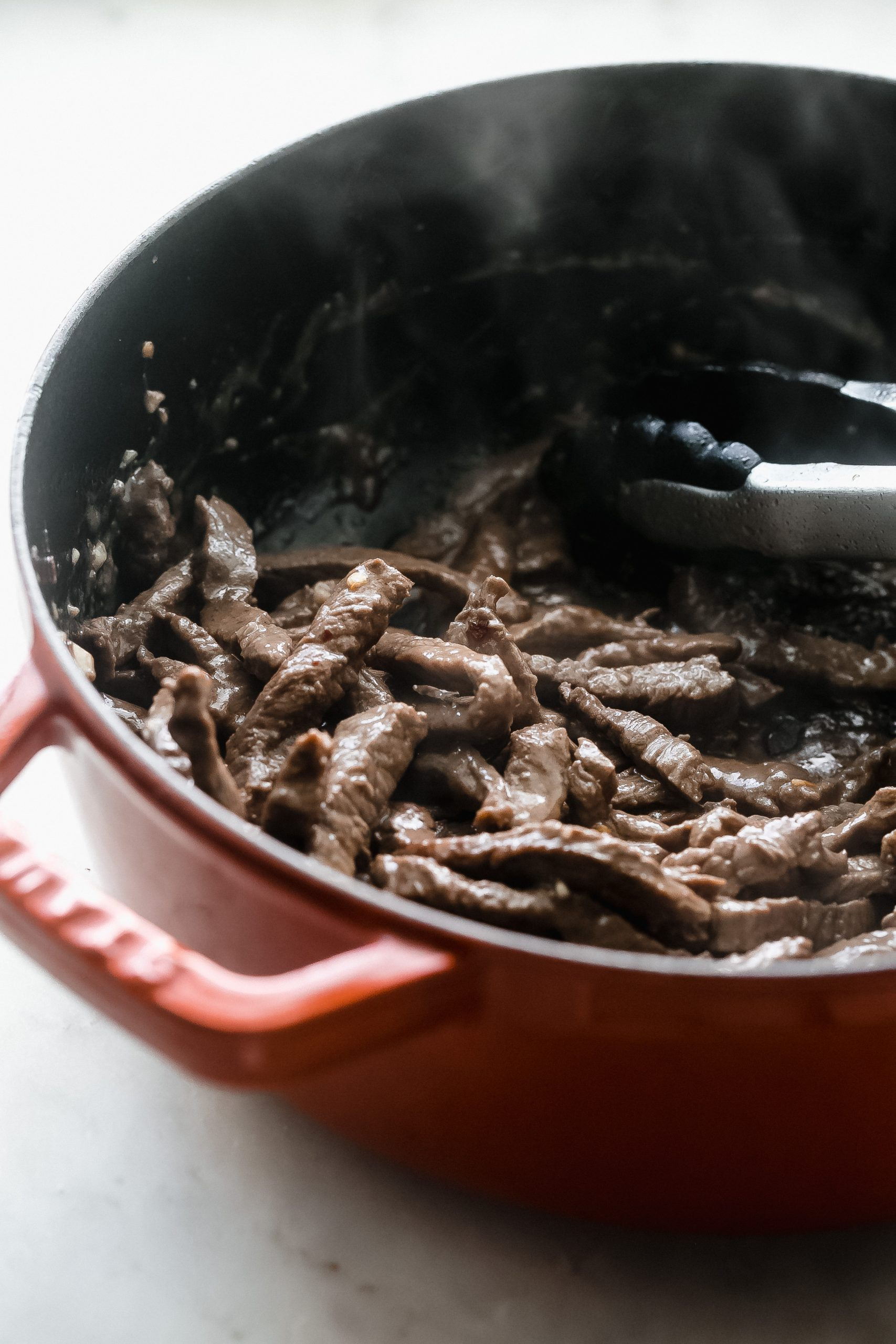 sautéed beef in cast iron pot with tongs