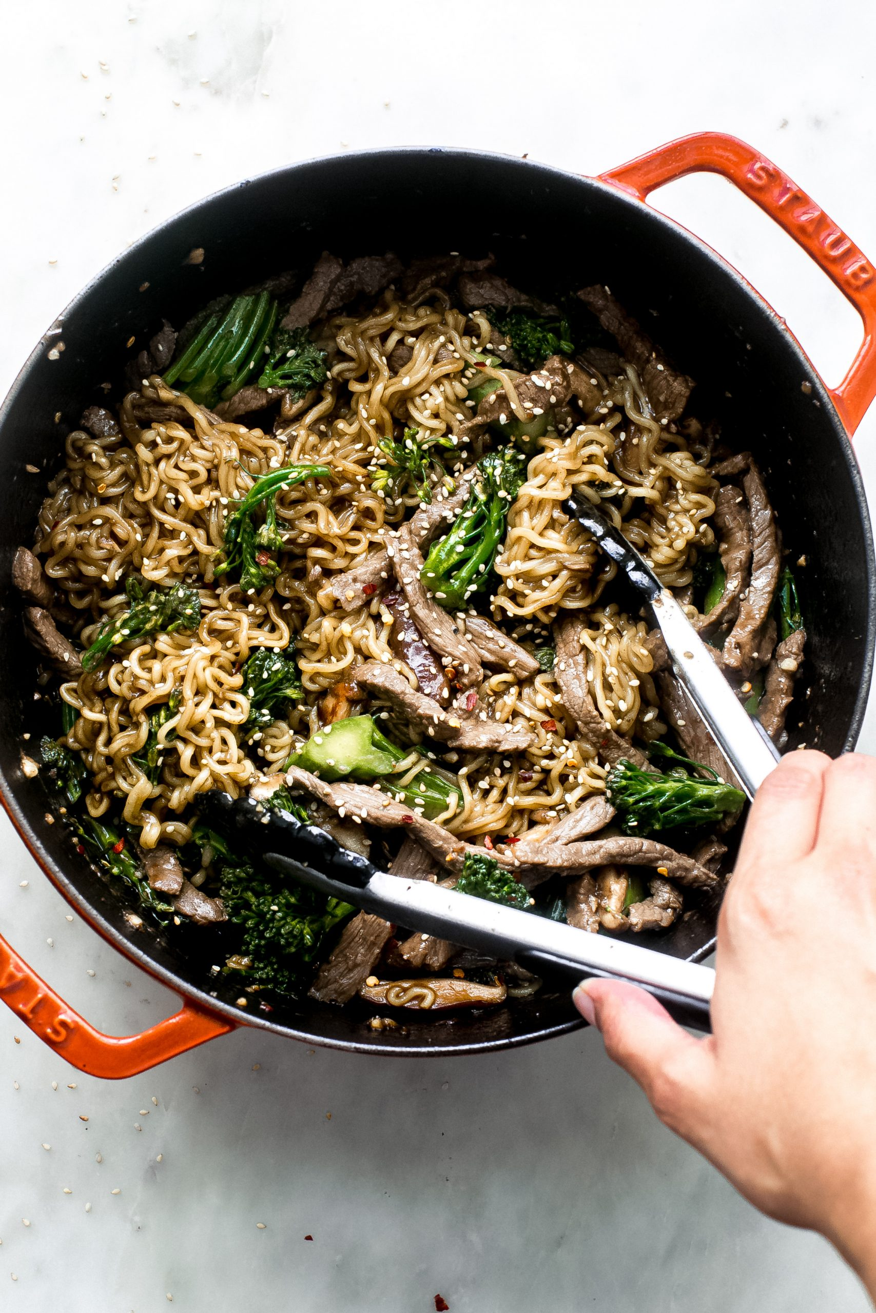 broccoli beef ramen being lifted with tongs from cast iron pot