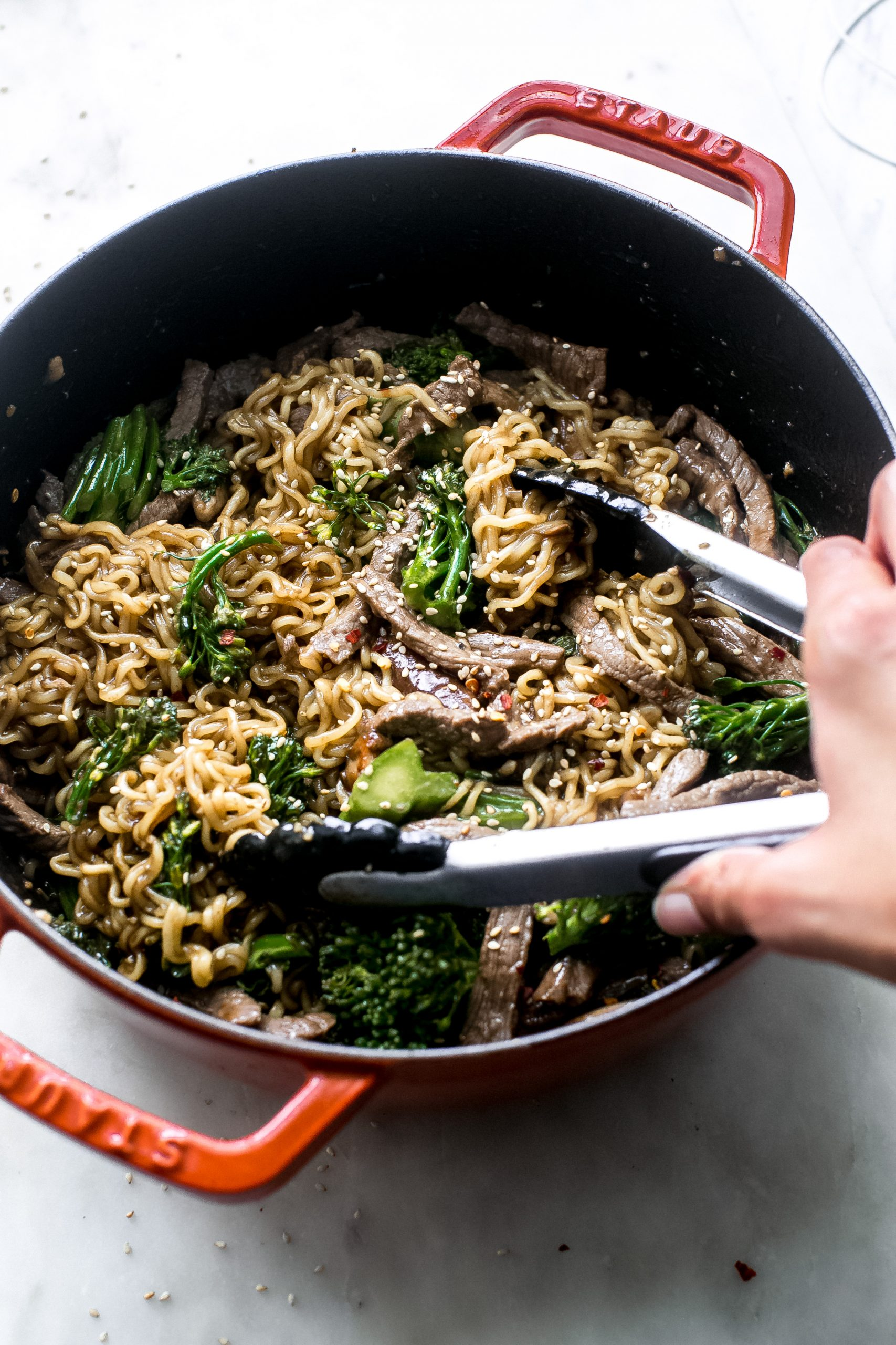 hand using tongs to life broccoli beef ramen