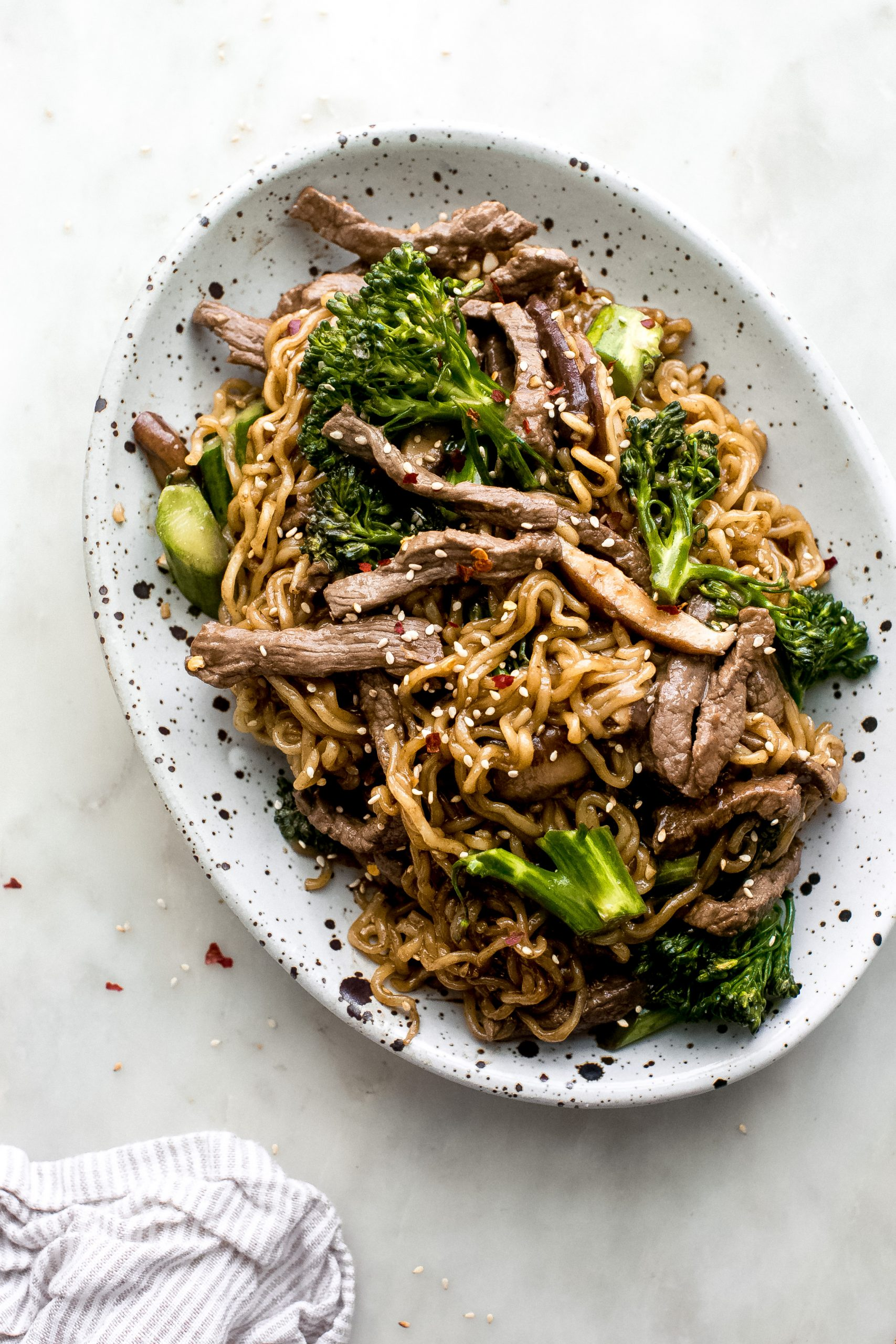 oval speckled plate with ramen noodles that were cooked with broccolini and strips of sautéed beef