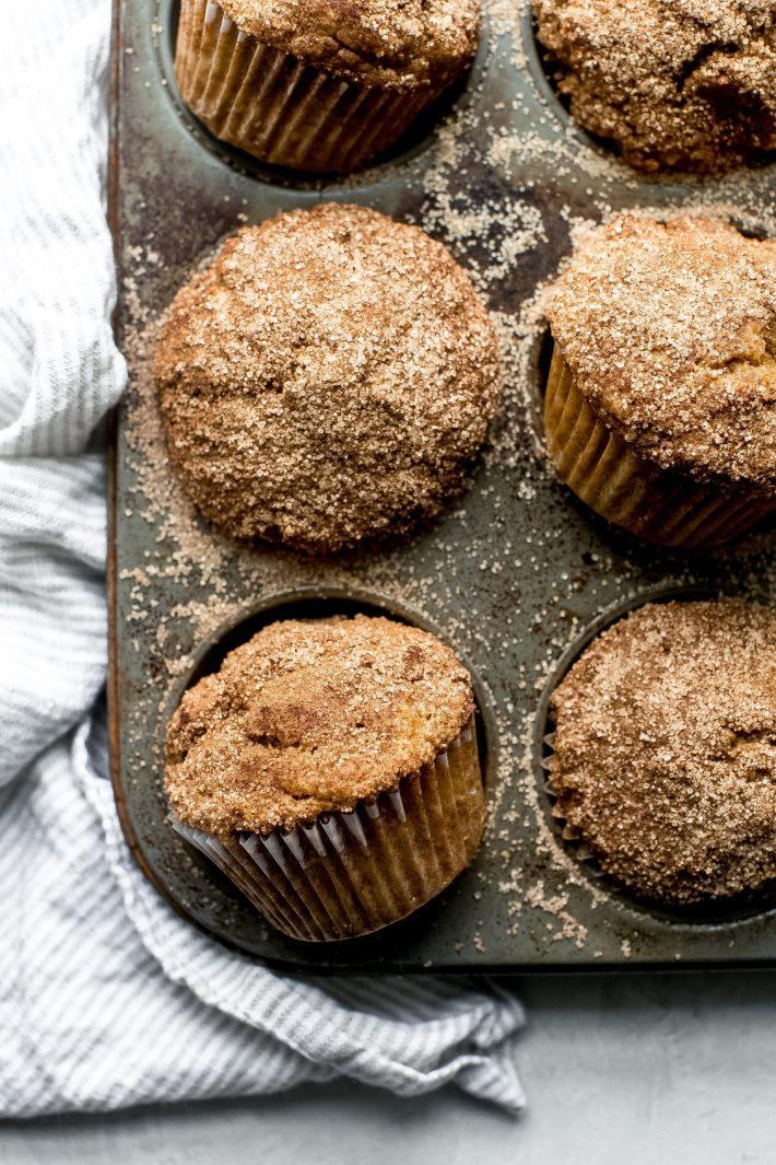 pumpkin snickerdoodle muffins in muffin pan with cinnamon sugar on top