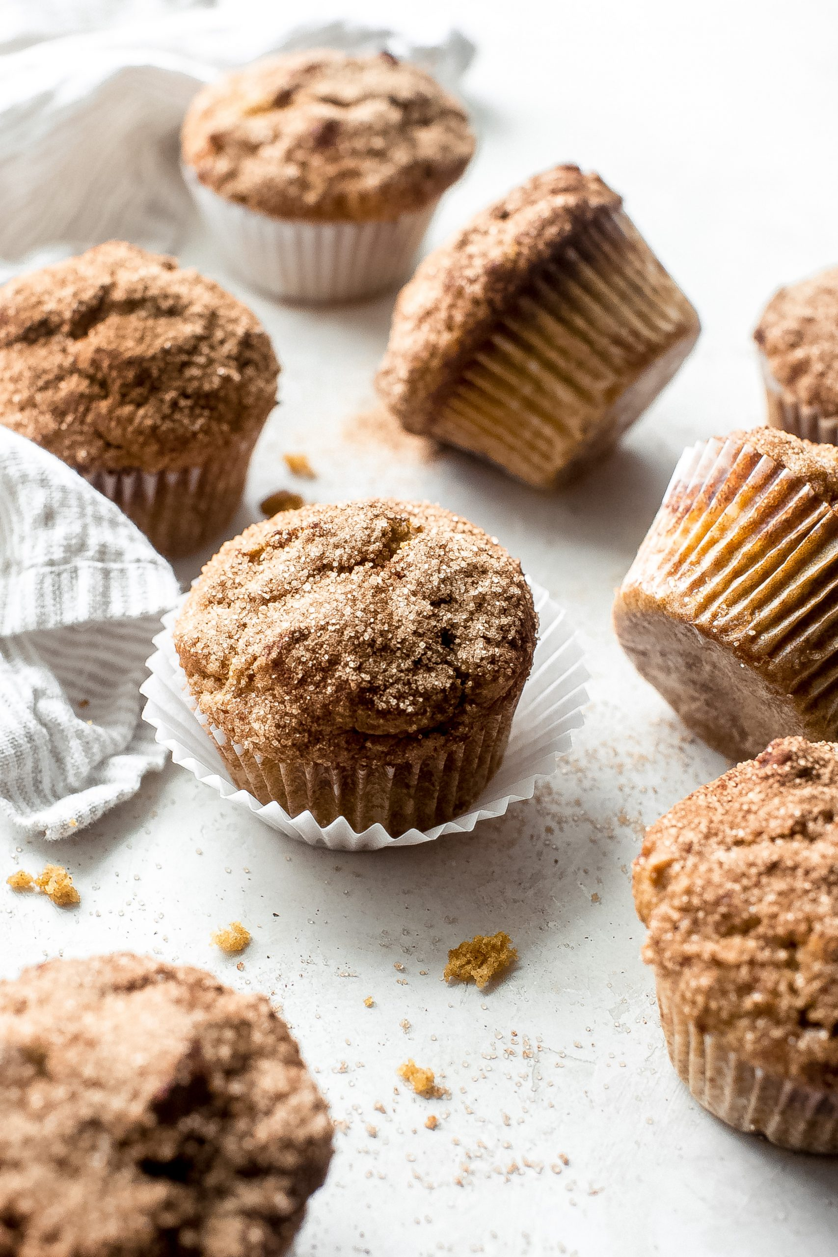 scattered muffin paper-lined pumpkin snickerdoodle muffins on a white surface