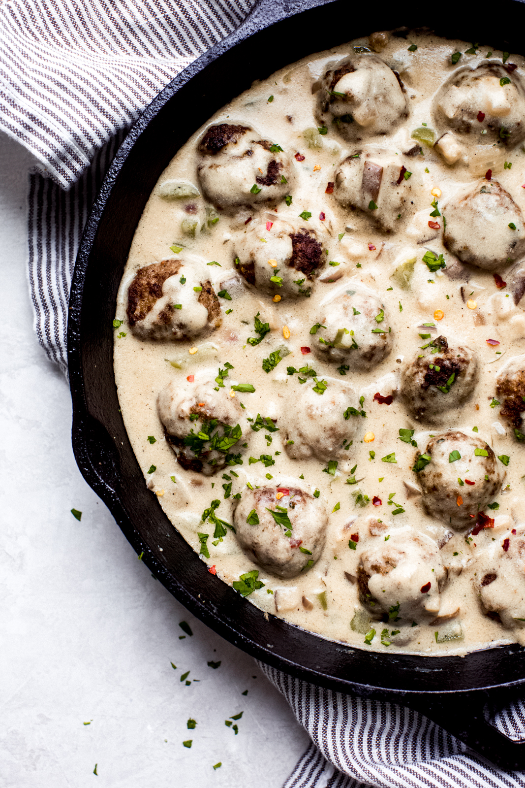 cast iron skillet with meatballs in cheese sauce