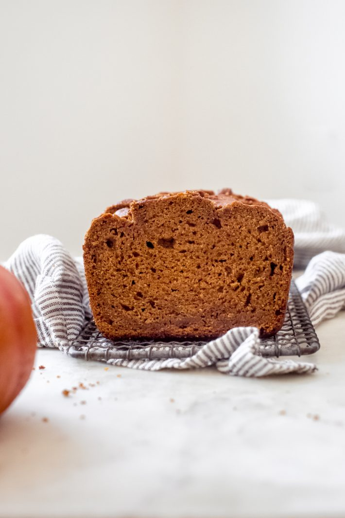 showing texture of pumpkin bread on wire rack placed on a tea towel on white marble