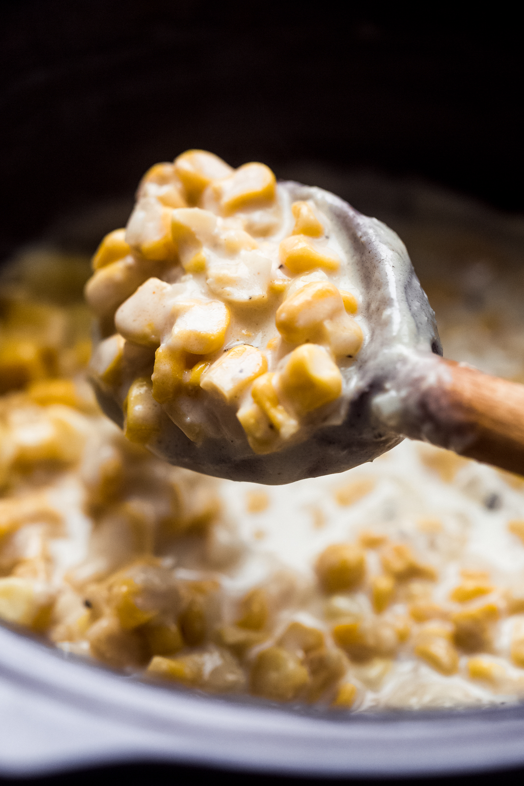 close up of creamed corn on wooden spoon