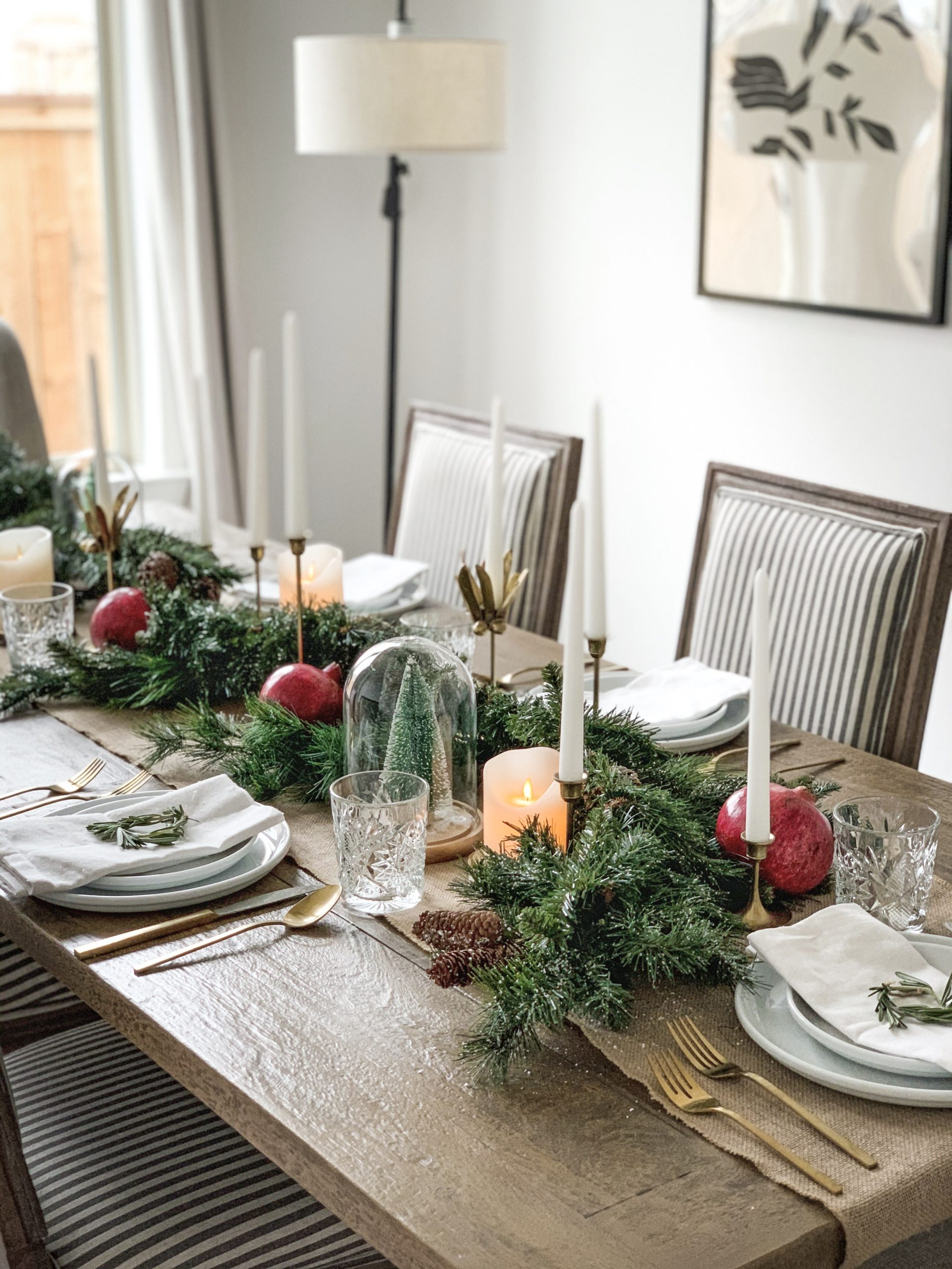 close up on dining table decorated with neutral greens and red pomegranates with gold tons