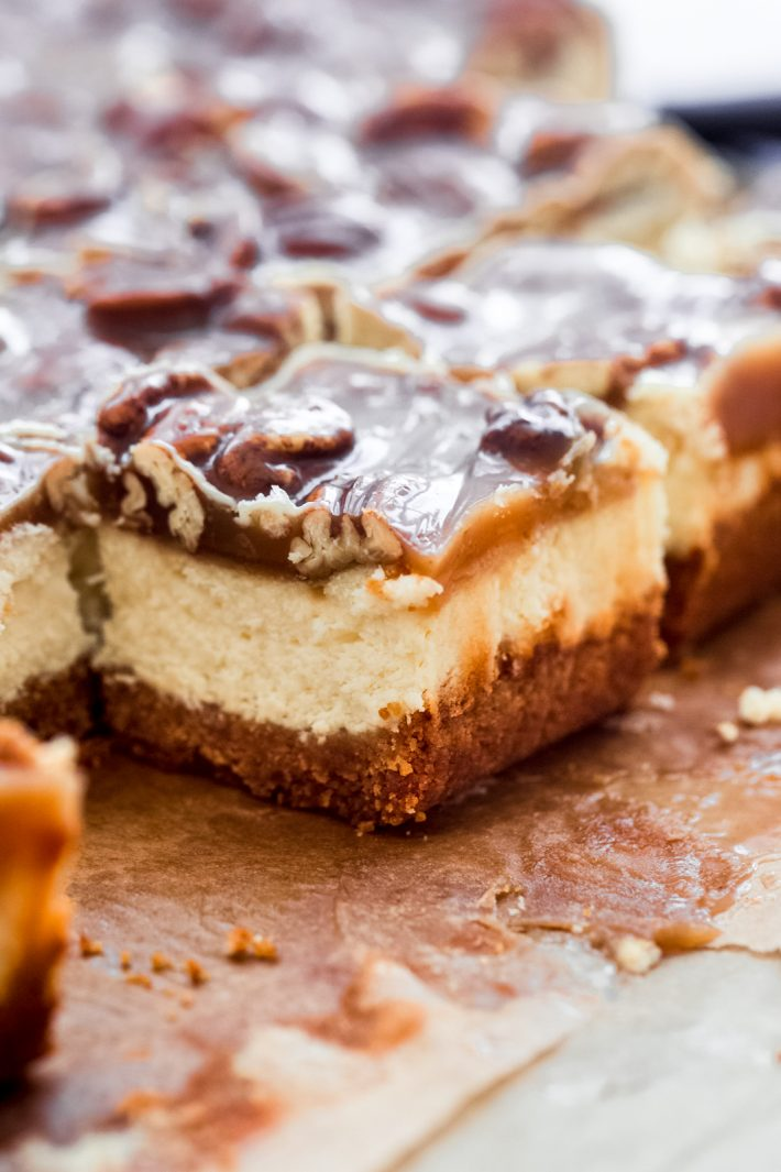 shiny caramel on pieces of pecan cheesecake bars