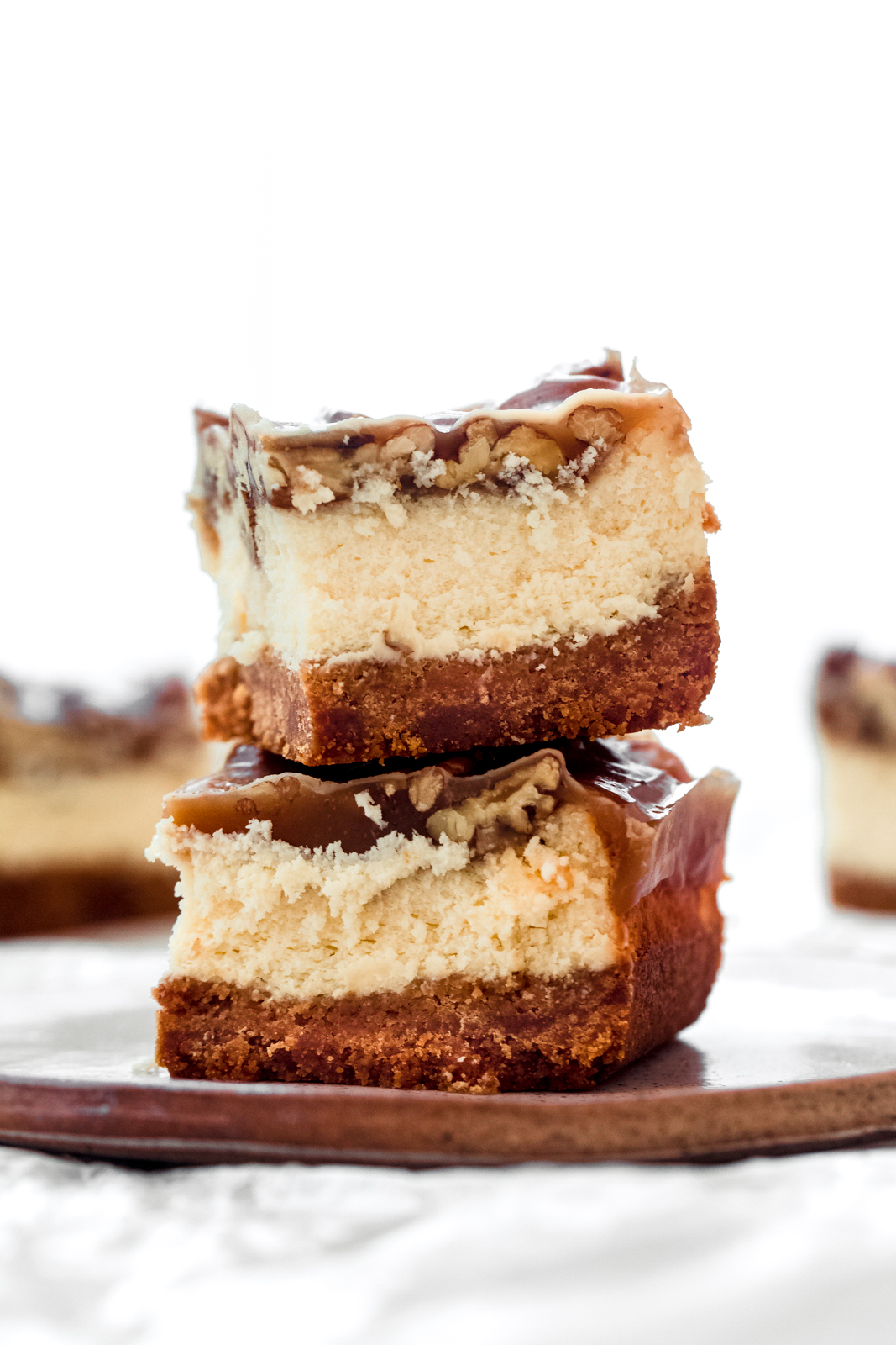 stack of two pecan pie cheesecake bars on a plate