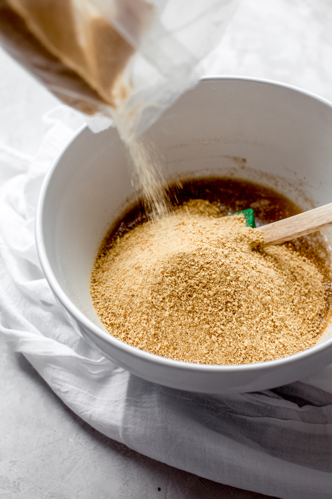 pouring graham cracker crumbs into a white bowl with spatula