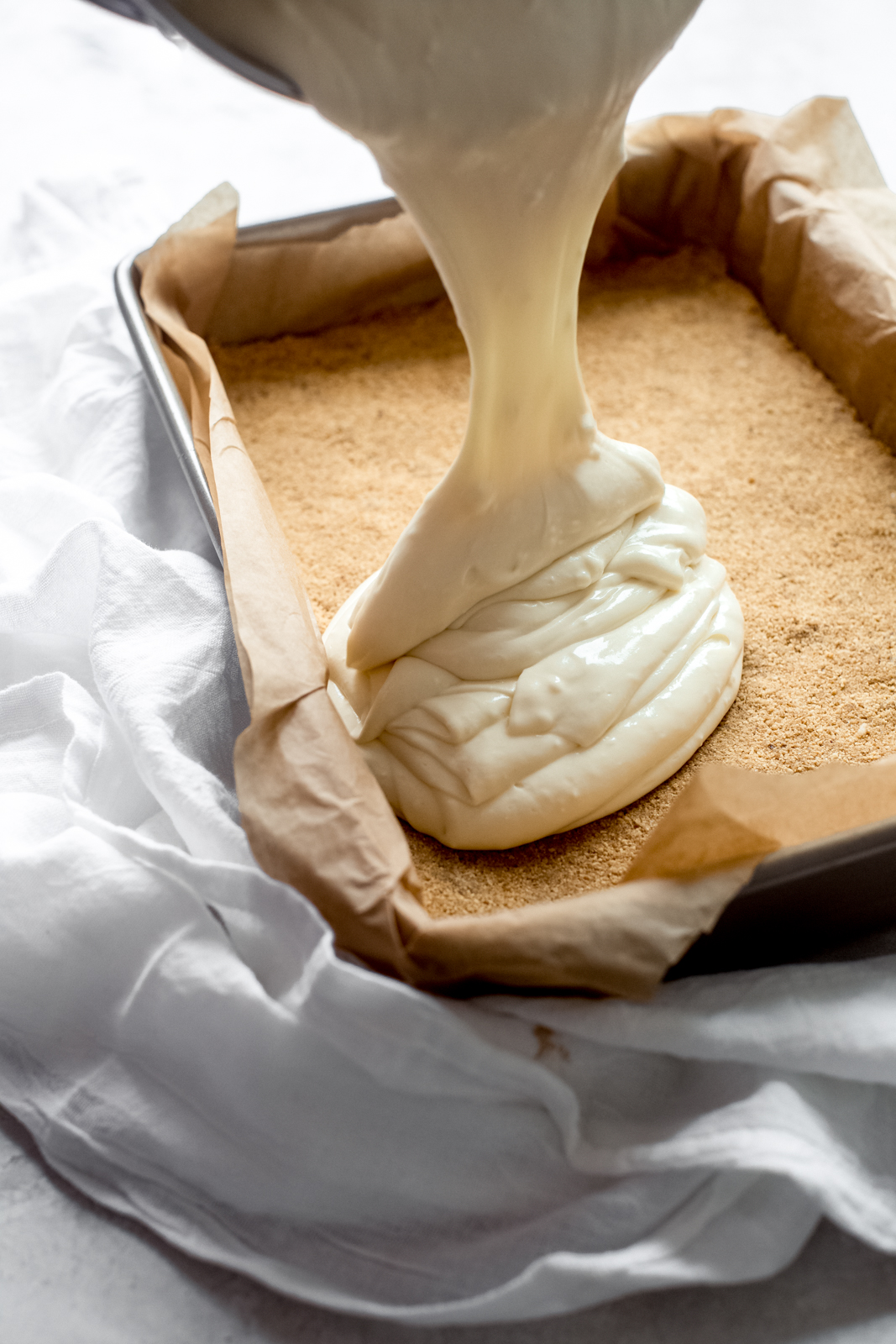 pouring cheesecake mixture over the prepared graham cracker crust in baking pan