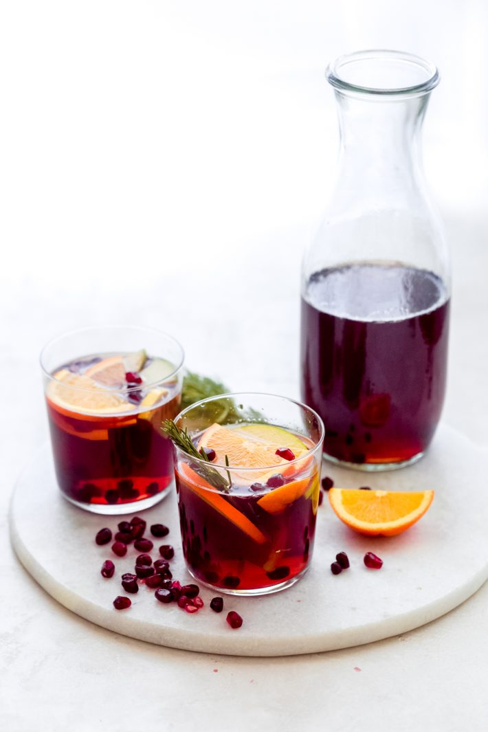 Festive Sangria Mocktail - Made with fresh fruit, juices, and a little fizz, this sangria cocktail is sure to be perfect for your holiday party! #sangriamocktail #mocktail #newyearsevecocktail #mocktails #sangria | Littlespicejar.com