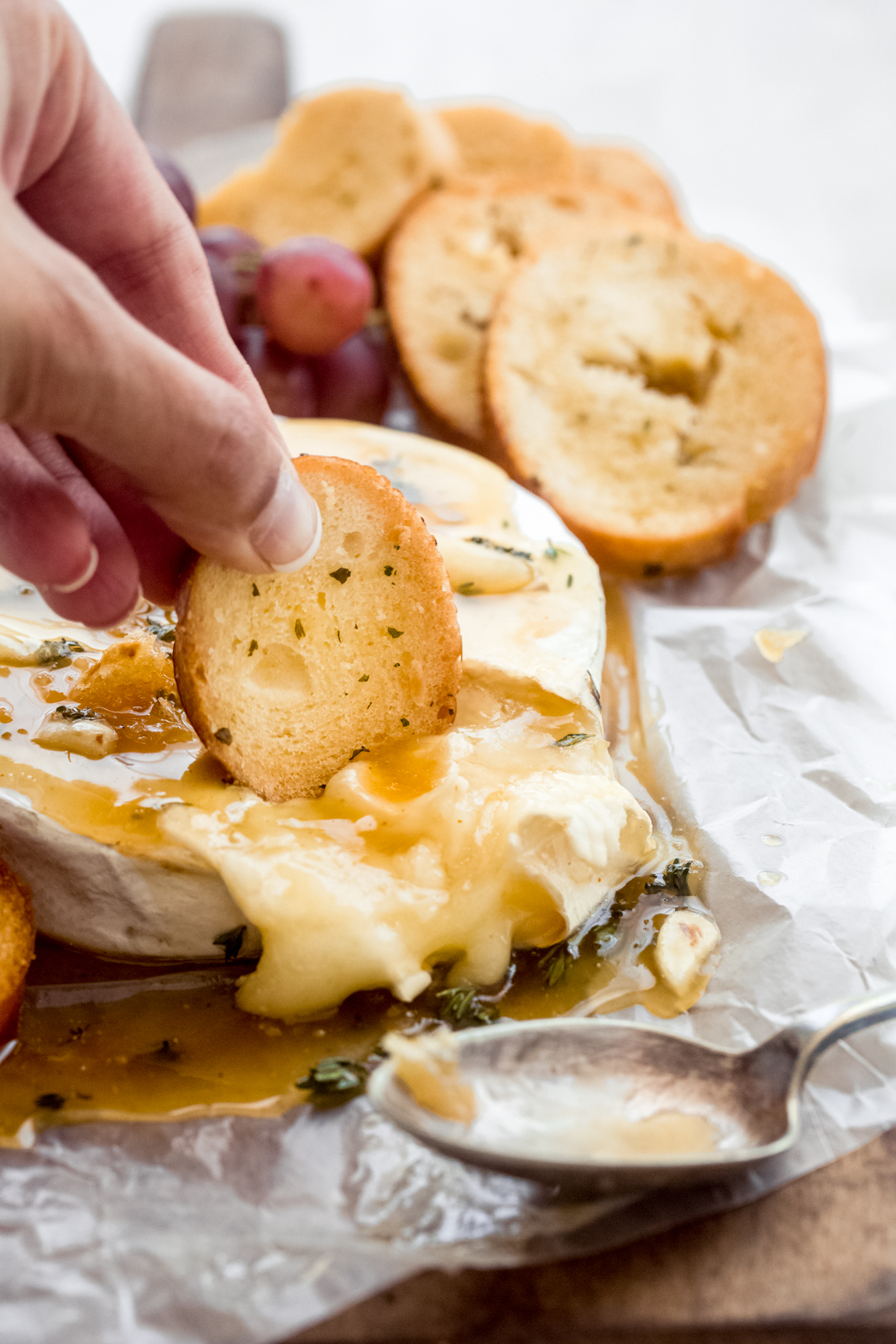 close up of bread dipped in melted brie cheese