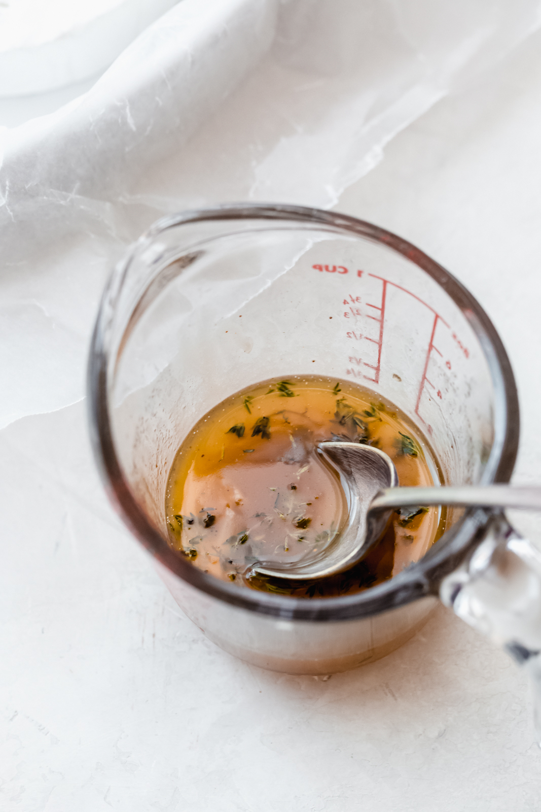 garlic herb and honey mixture in measuring glass for baked brie