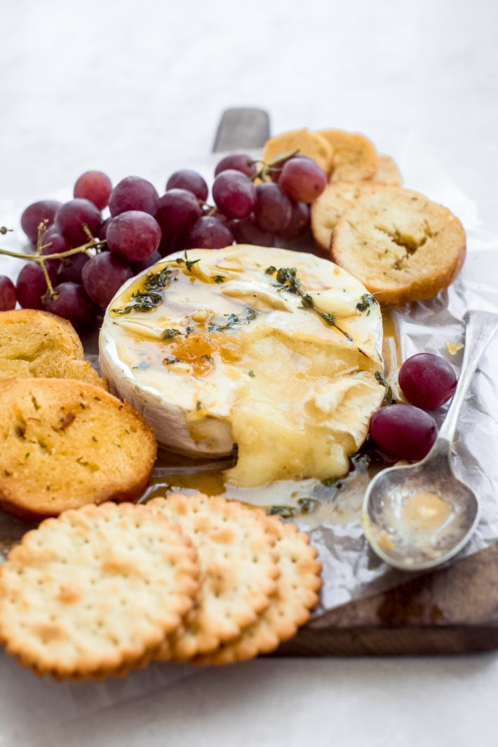 Herb Garlic Baked Brie - A new twist on the classic Baked Brie! We bake the brie topped with a thyme honey butter and guaranteed, this will disappear in no time! #bakedbrie #appetizers #holidayappetizers #easyappetizers #honeybakedbrie #briecheese | Littlespicejar.com