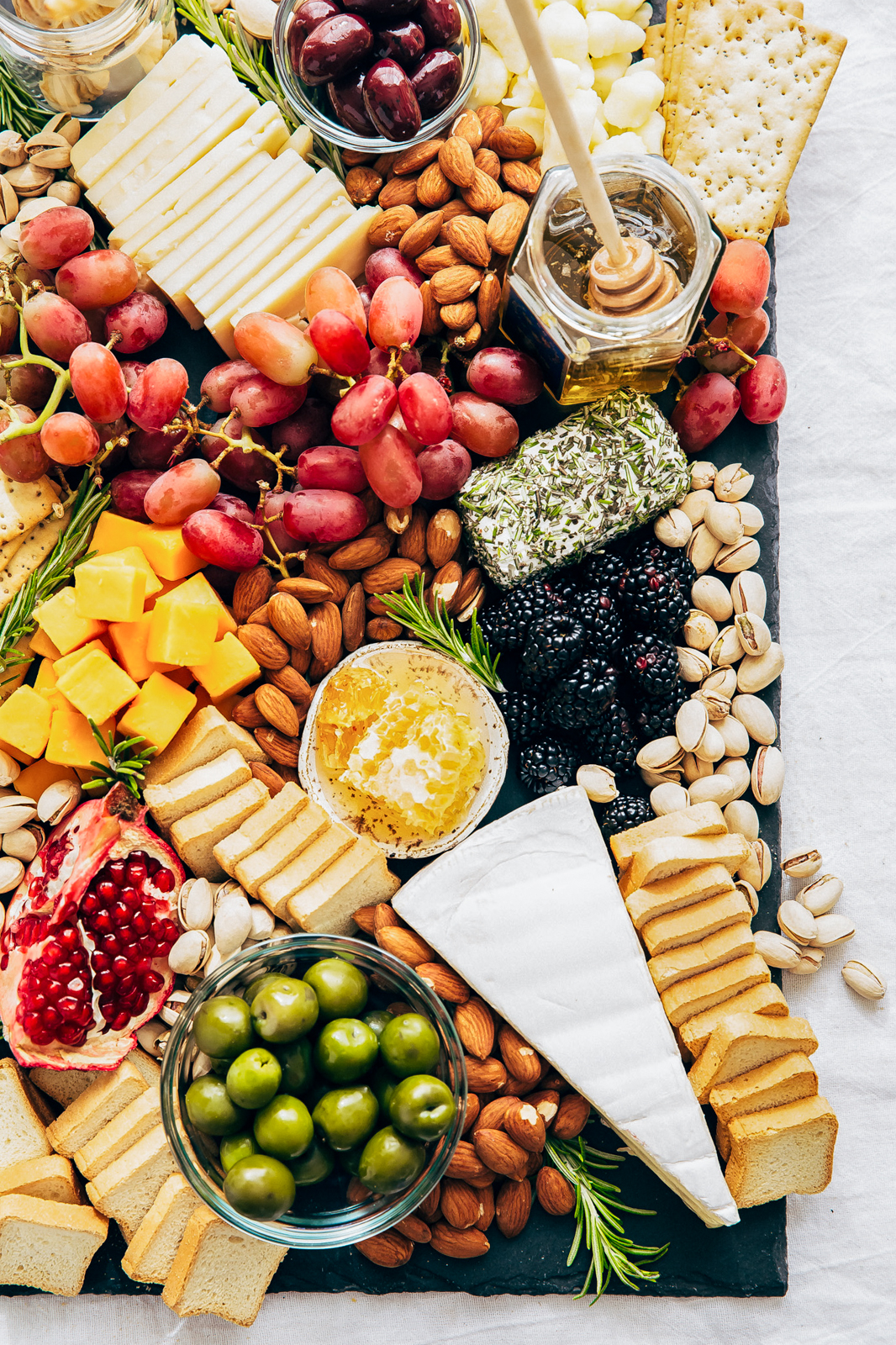 various cheeses, fruits, nuts, and honey on a black cheese board