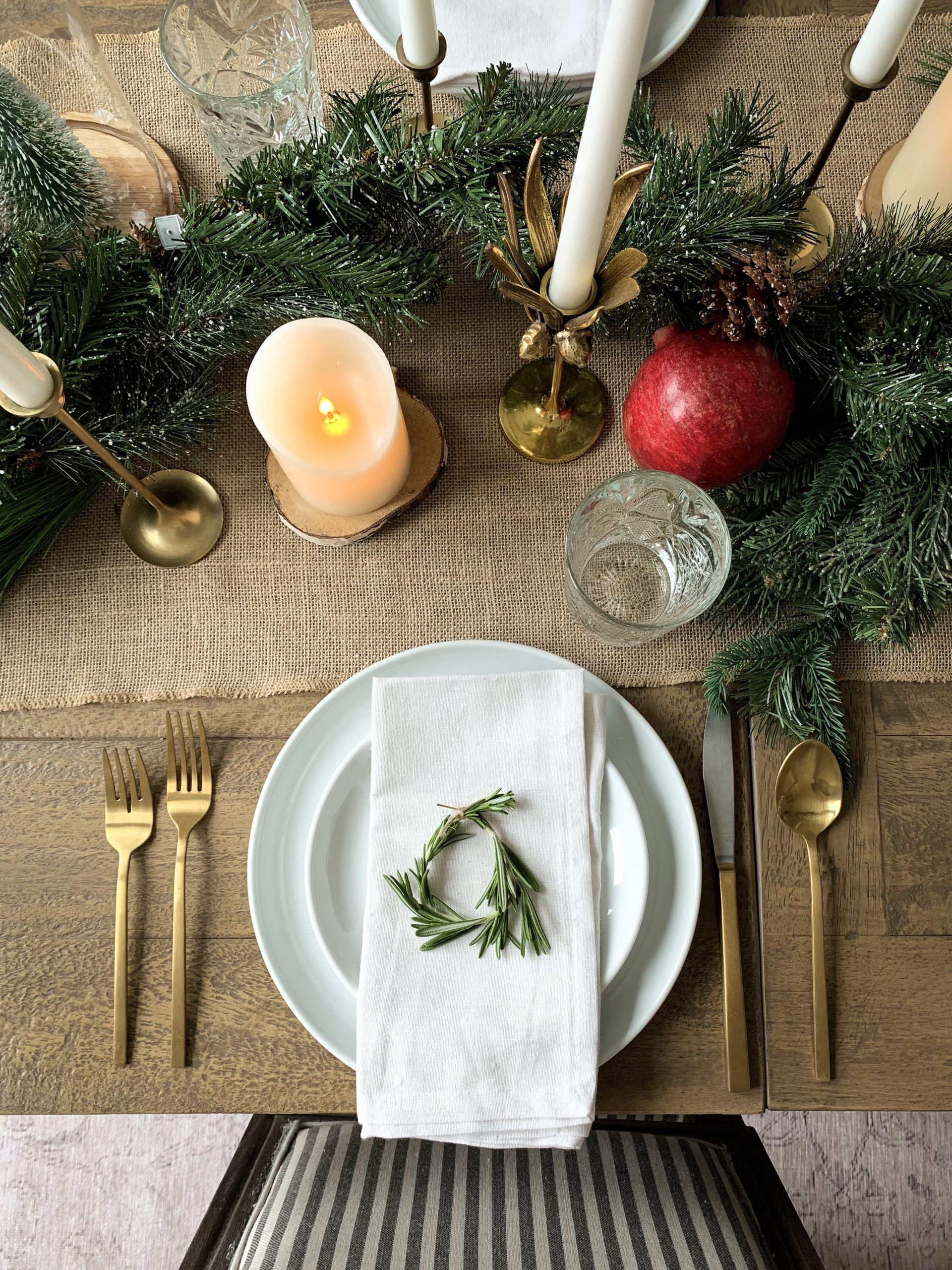 close up of place setting for a holiday tables cape with neutral tones with evergreens