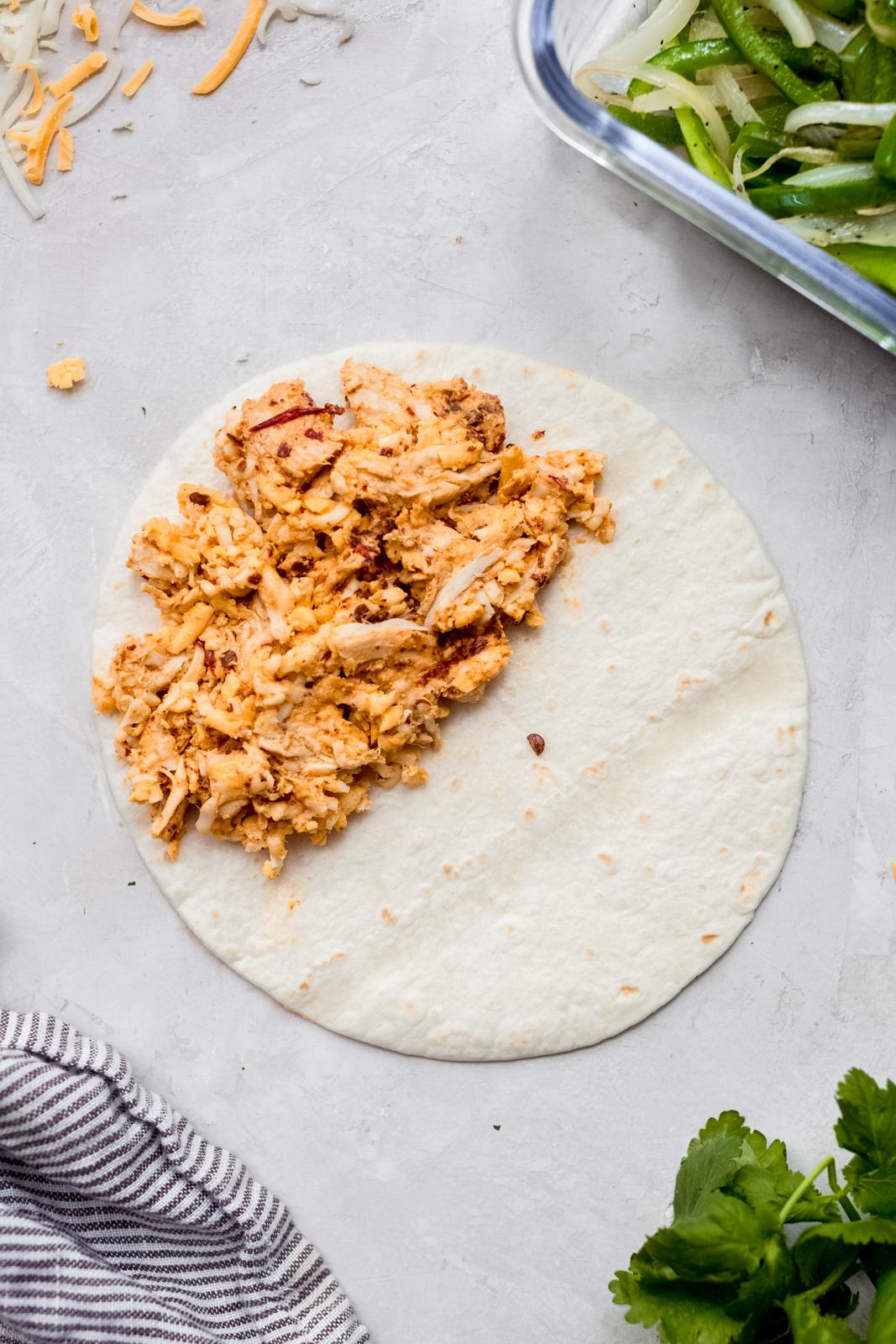 chicken quesadilla mixture on half of a tortilla