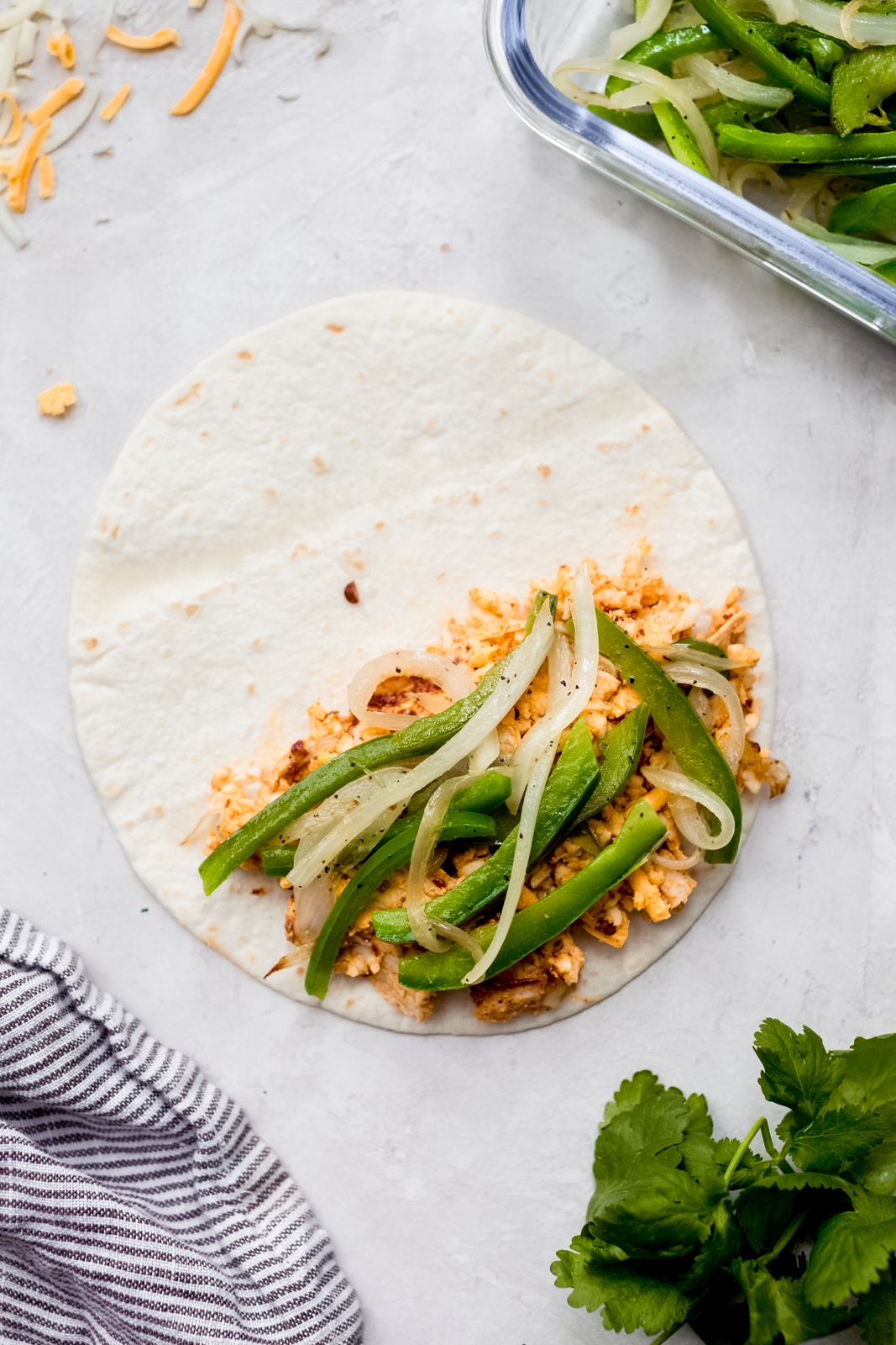 chicken mixture and peppers and onions on one side of a tortilla