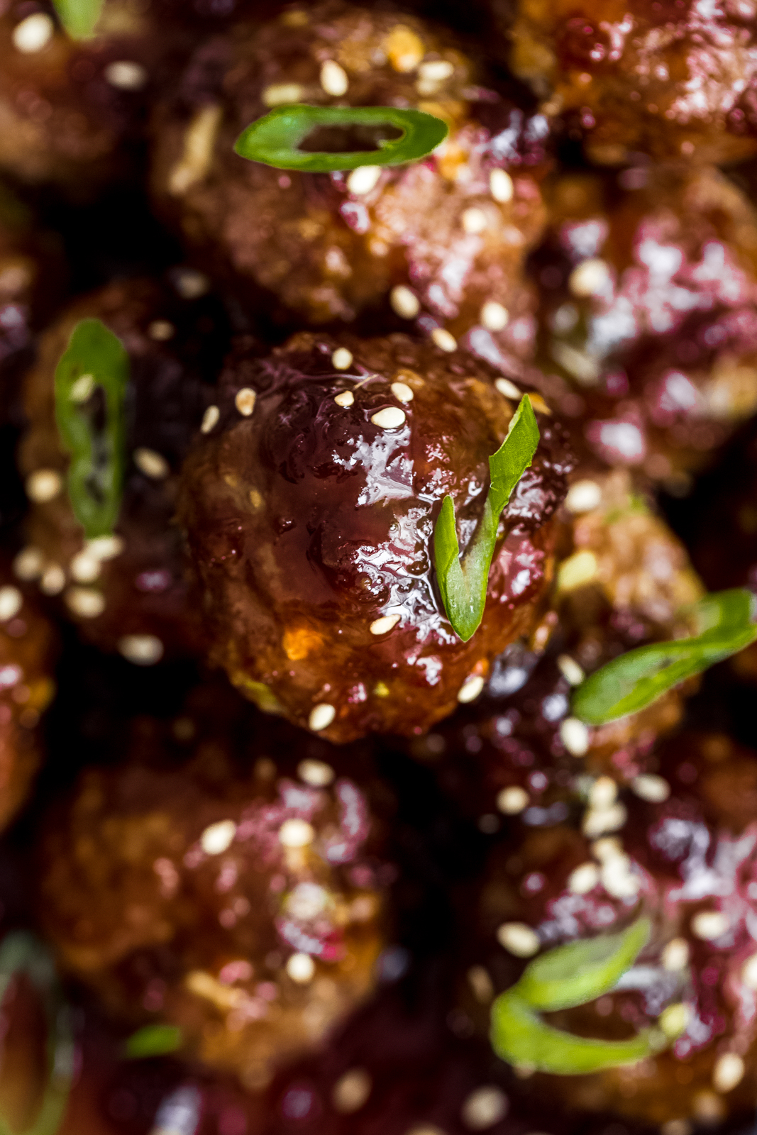 sticky sauce on beef meatballs topped with scallions and sesame seeds