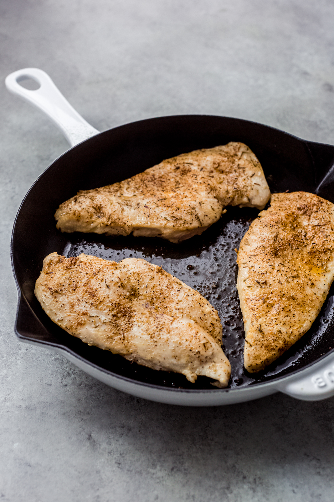 skillet with seasoned and seared chicken breasts ready for the oven