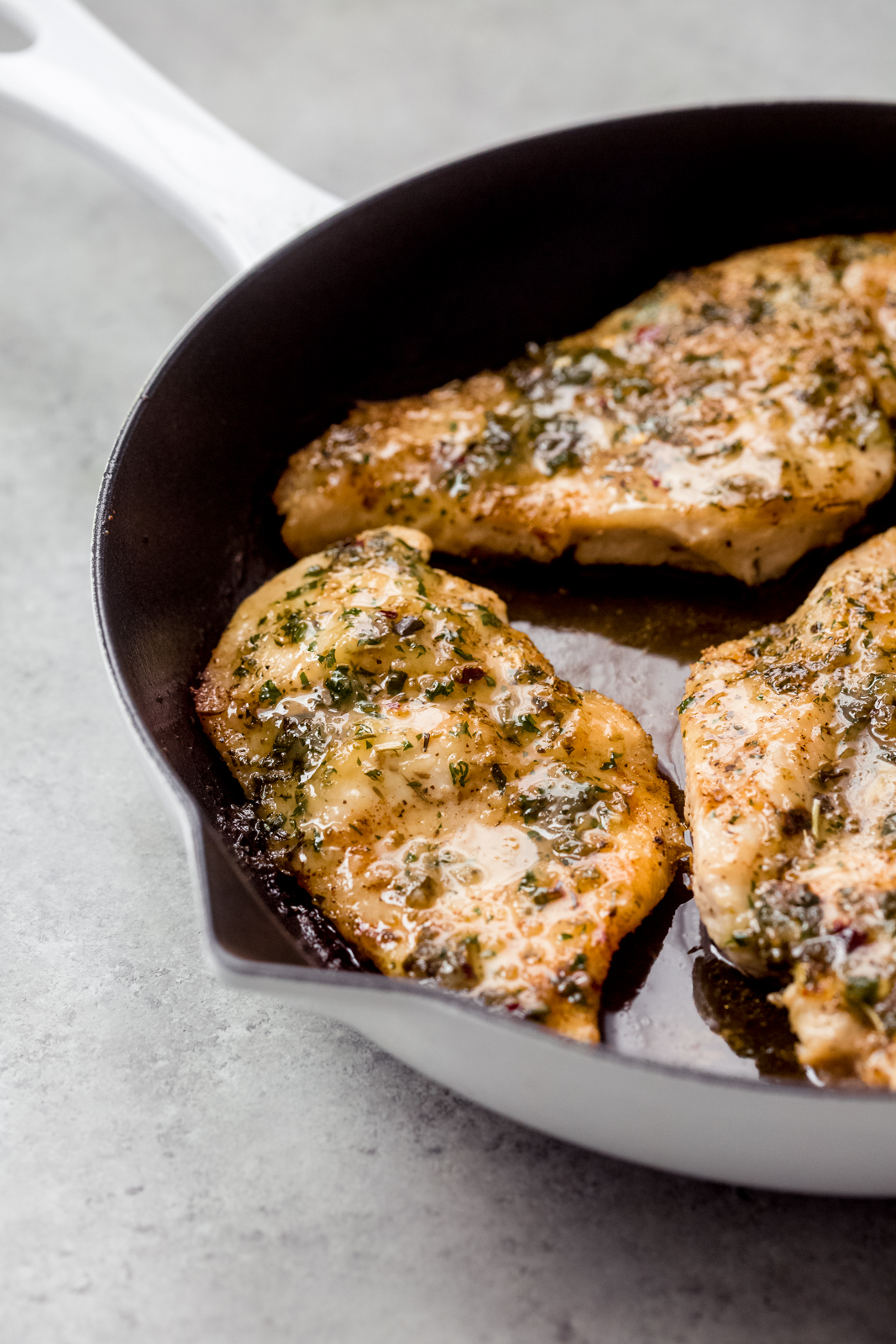 glistening garlic herb butter basted chicken in a skillet