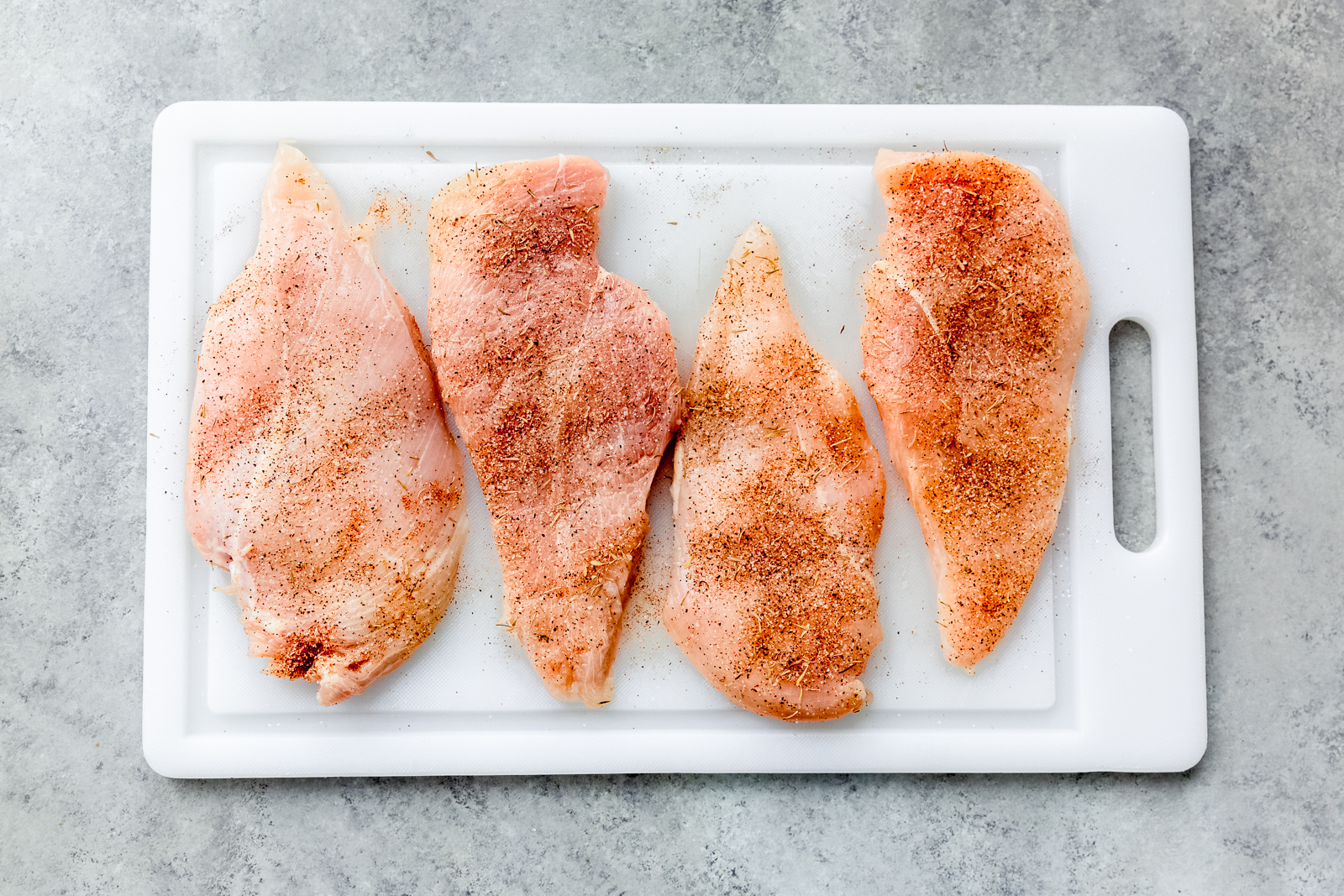 white cutting board with raw chicken sprinkled with seasoning
