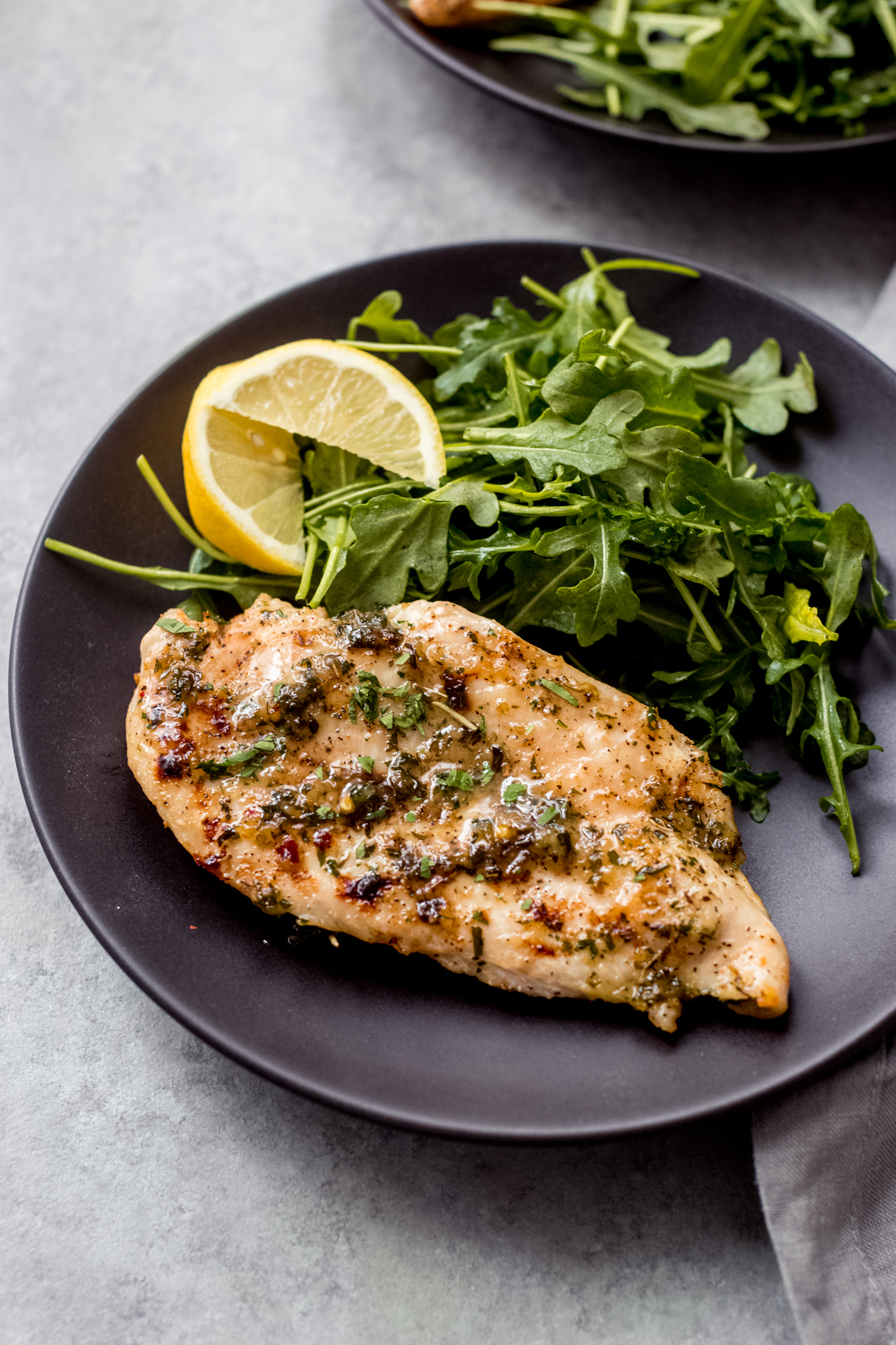 black plate with baked chicken breast, lemon slices, and fresh arugula