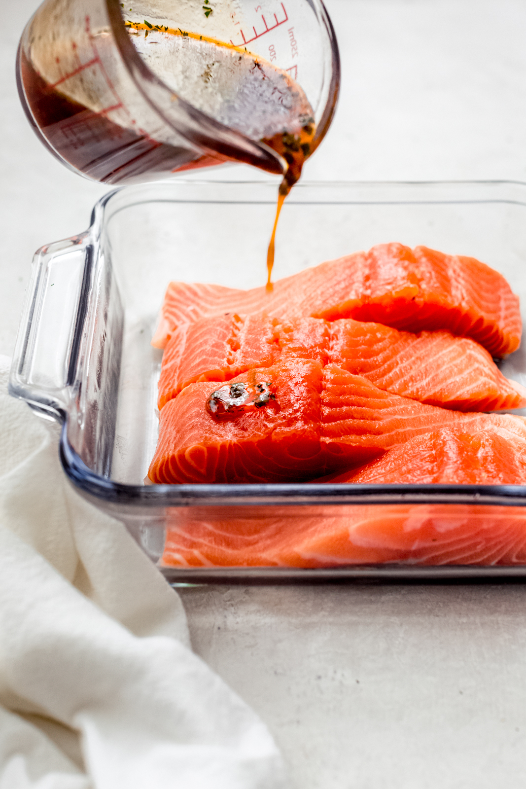 pouring marinade on salmon filets in glass dish