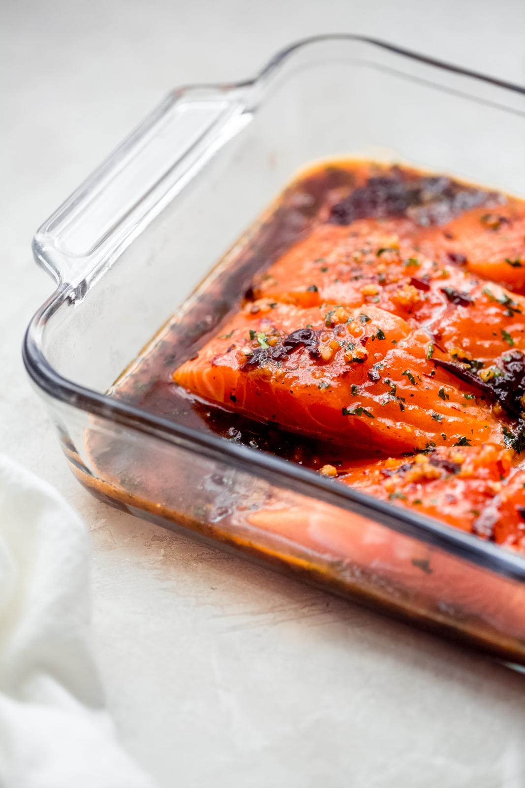 salmon filets marinating in glass baking dish