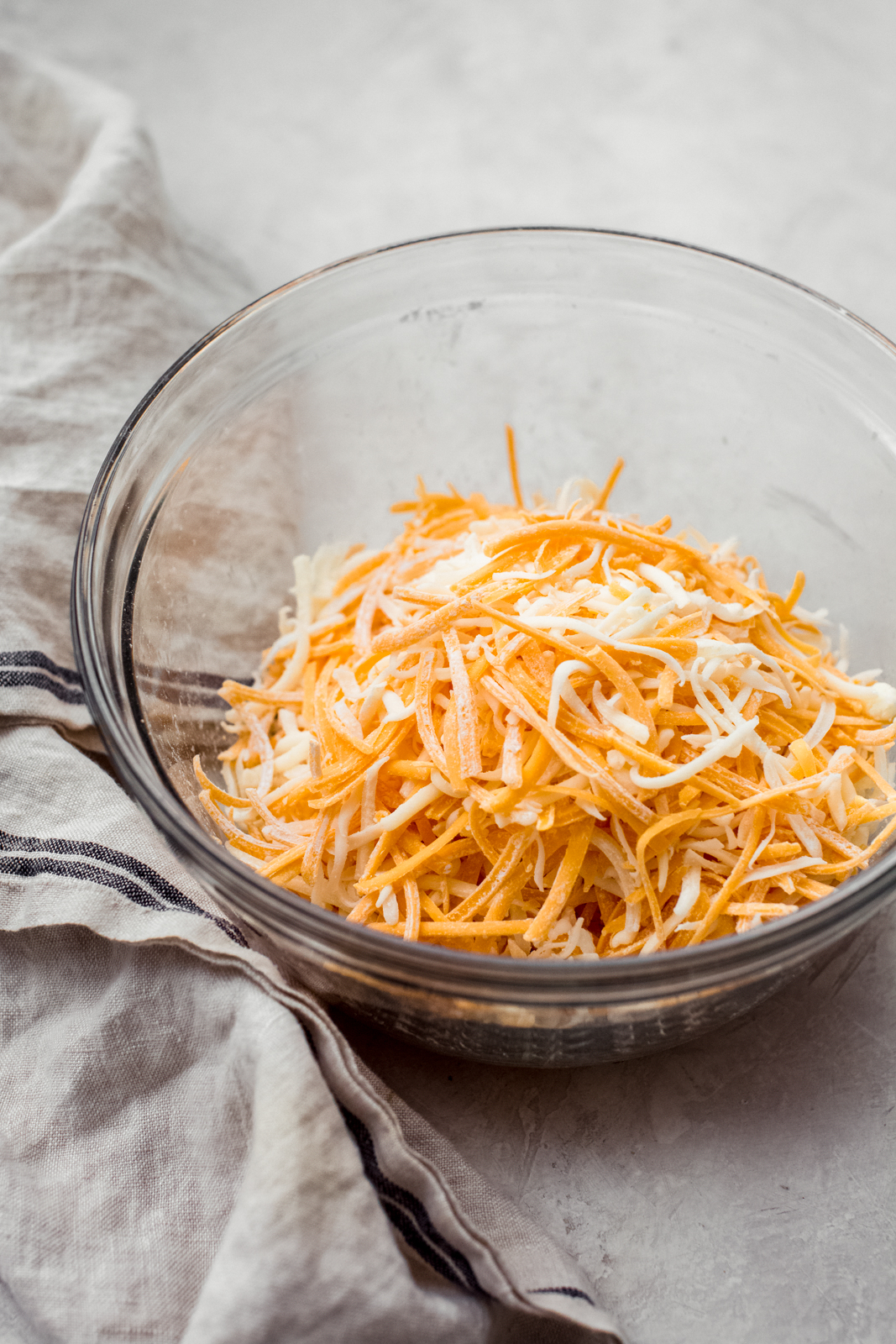 shredded cheese in glass bowl