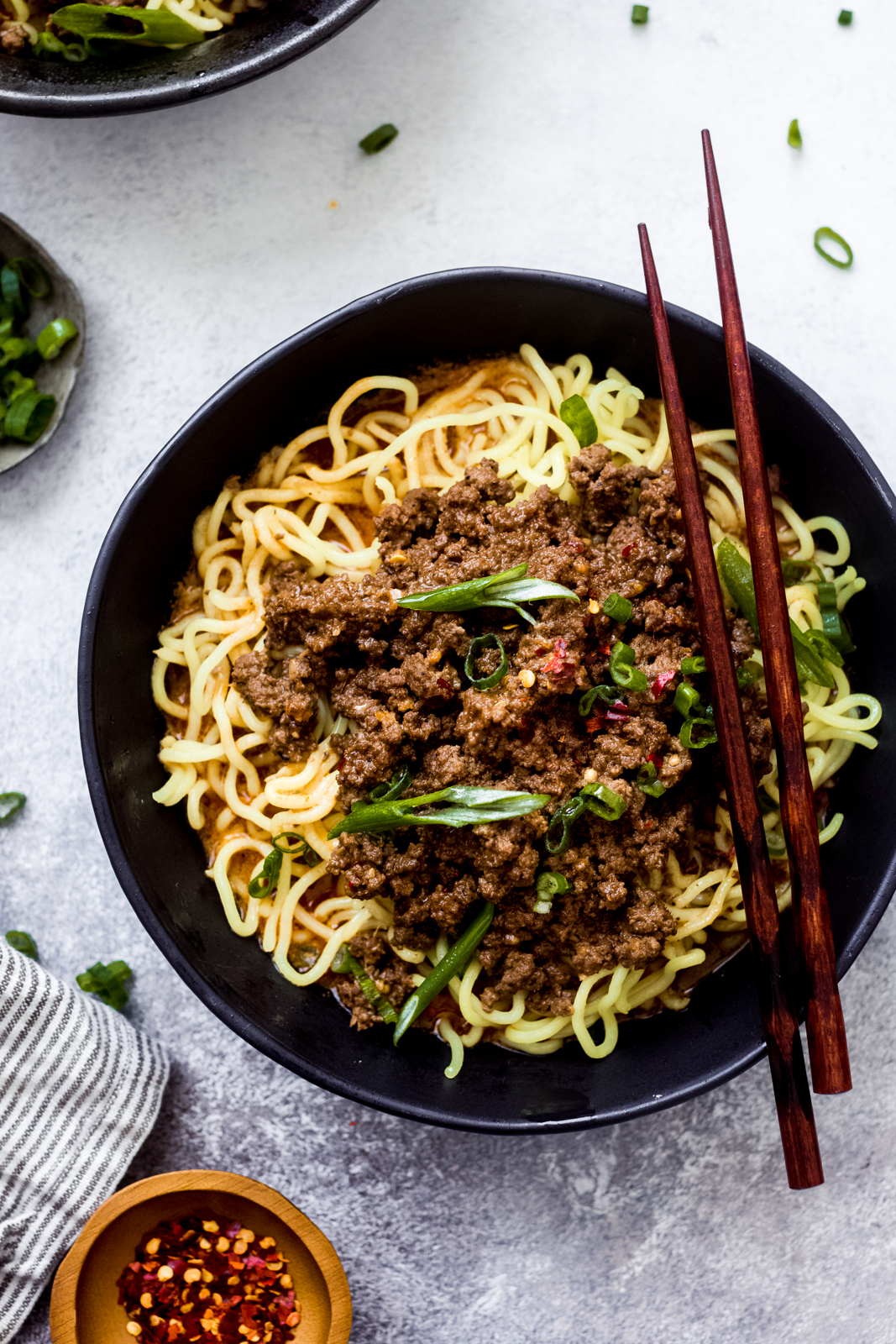 black bowl with chopsticks resting on top with noodles and meat mixture in bowl