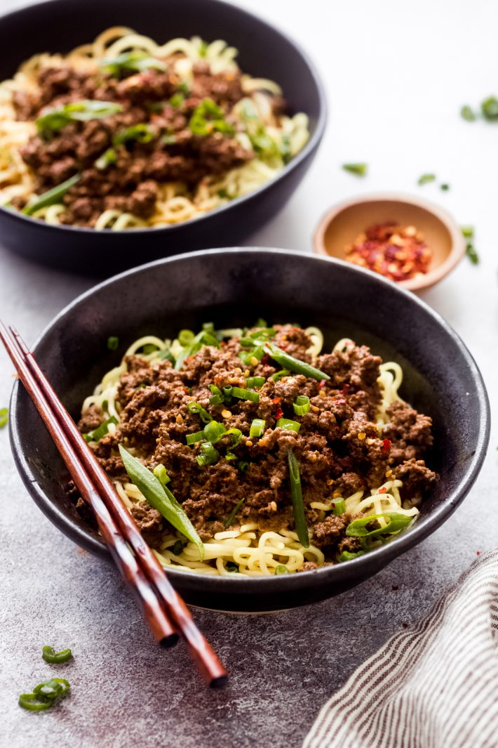 black bowl with noodles topped with dan dan mixture and chopsticks