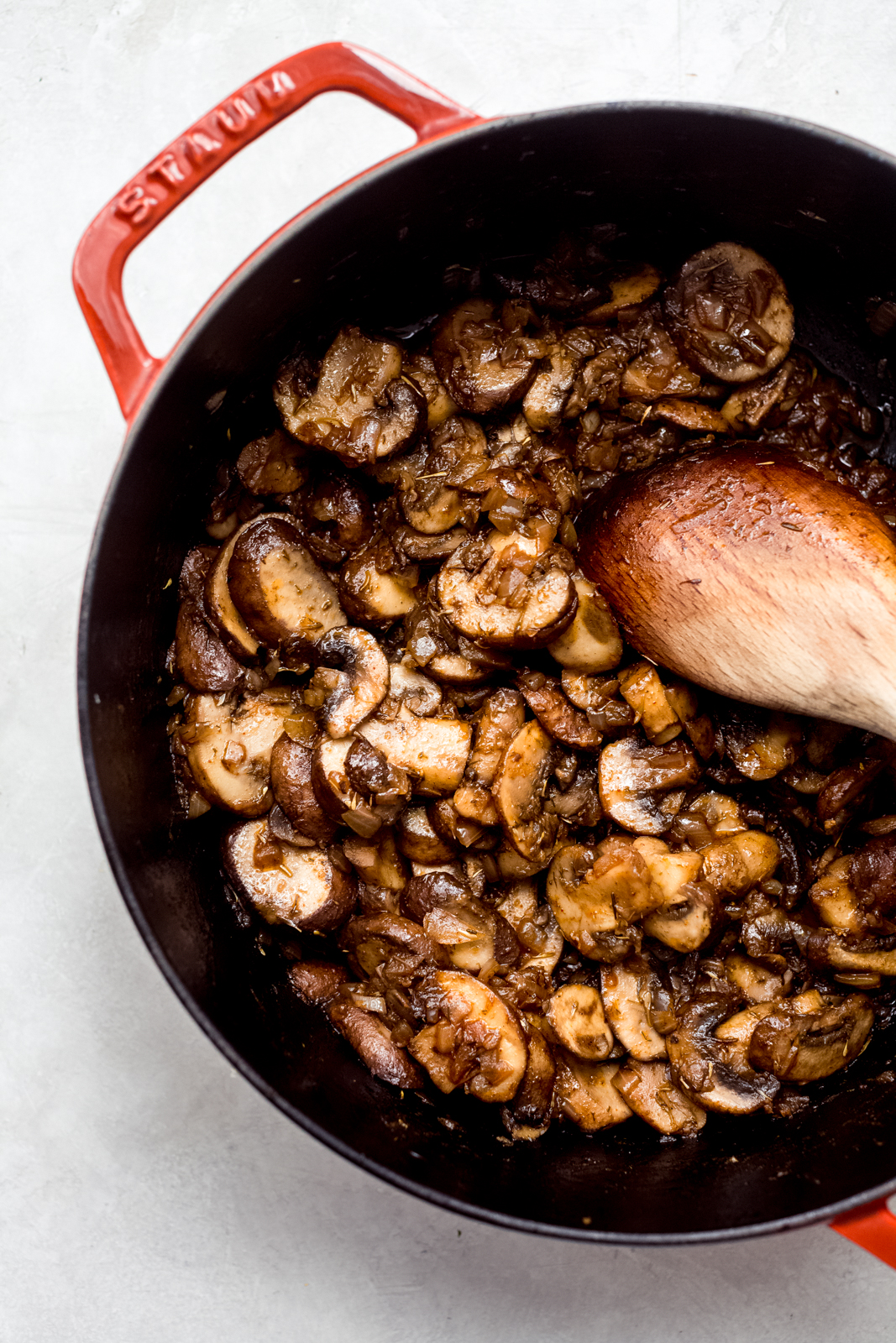 sautéed mushrooms in a pot with wooden spoon