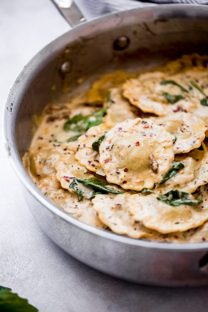 ravioli in a skillet with wilted spinach