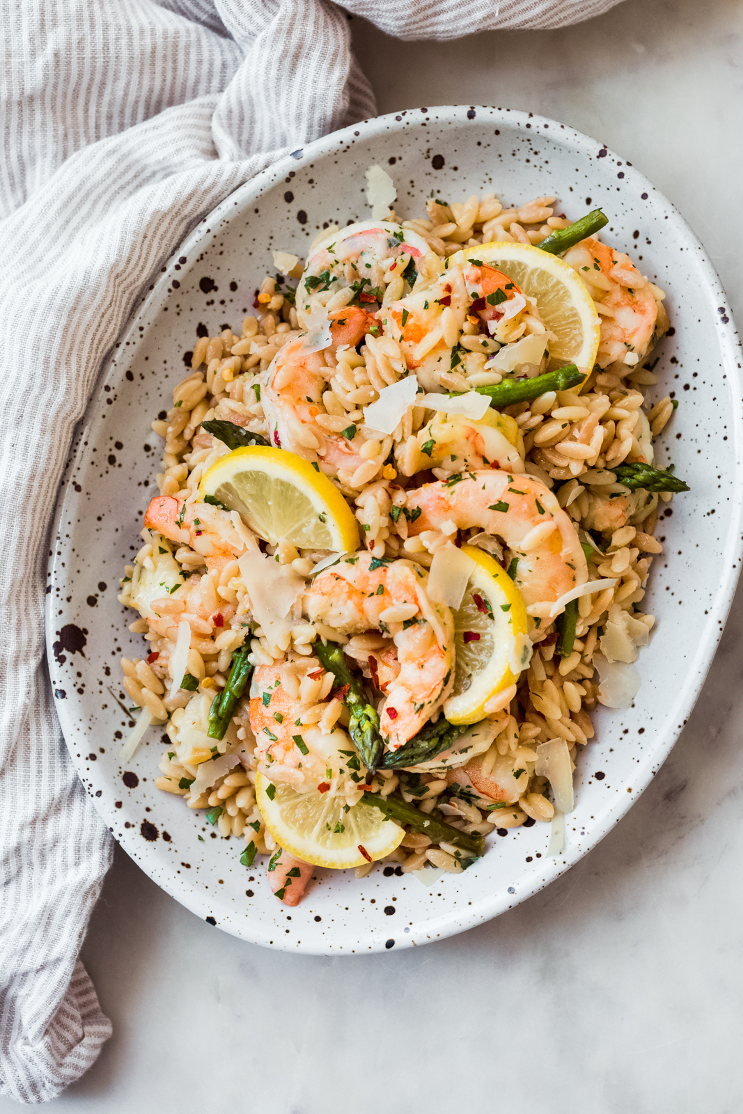 oval speckled dish with prepared orzo scampi with fresh lemon slices