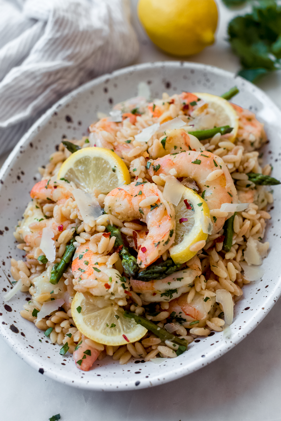 speckled oval plate with shrimp and orzo and asparagus