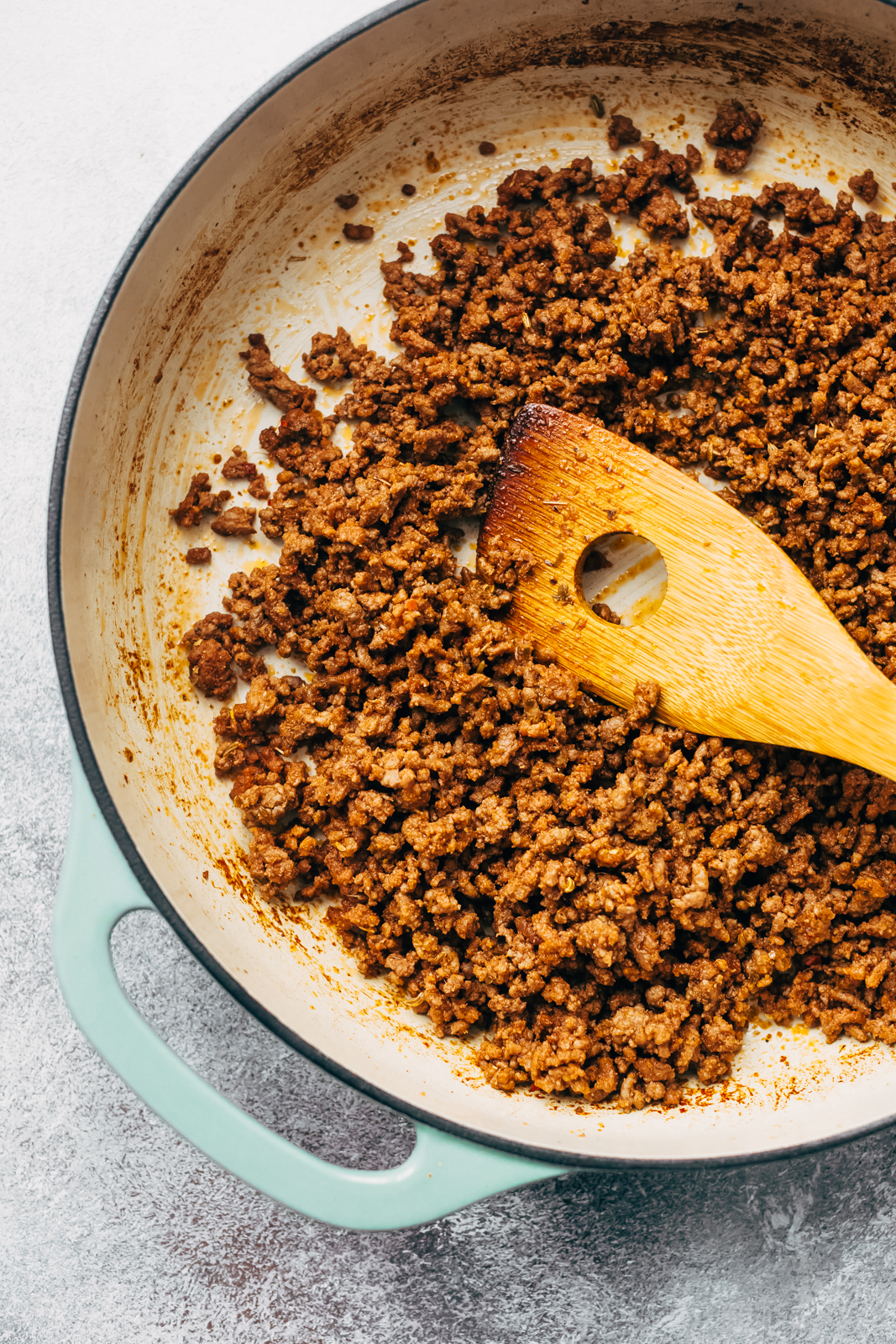 Ground beef mixture in cast iron dish with wooden spoon
