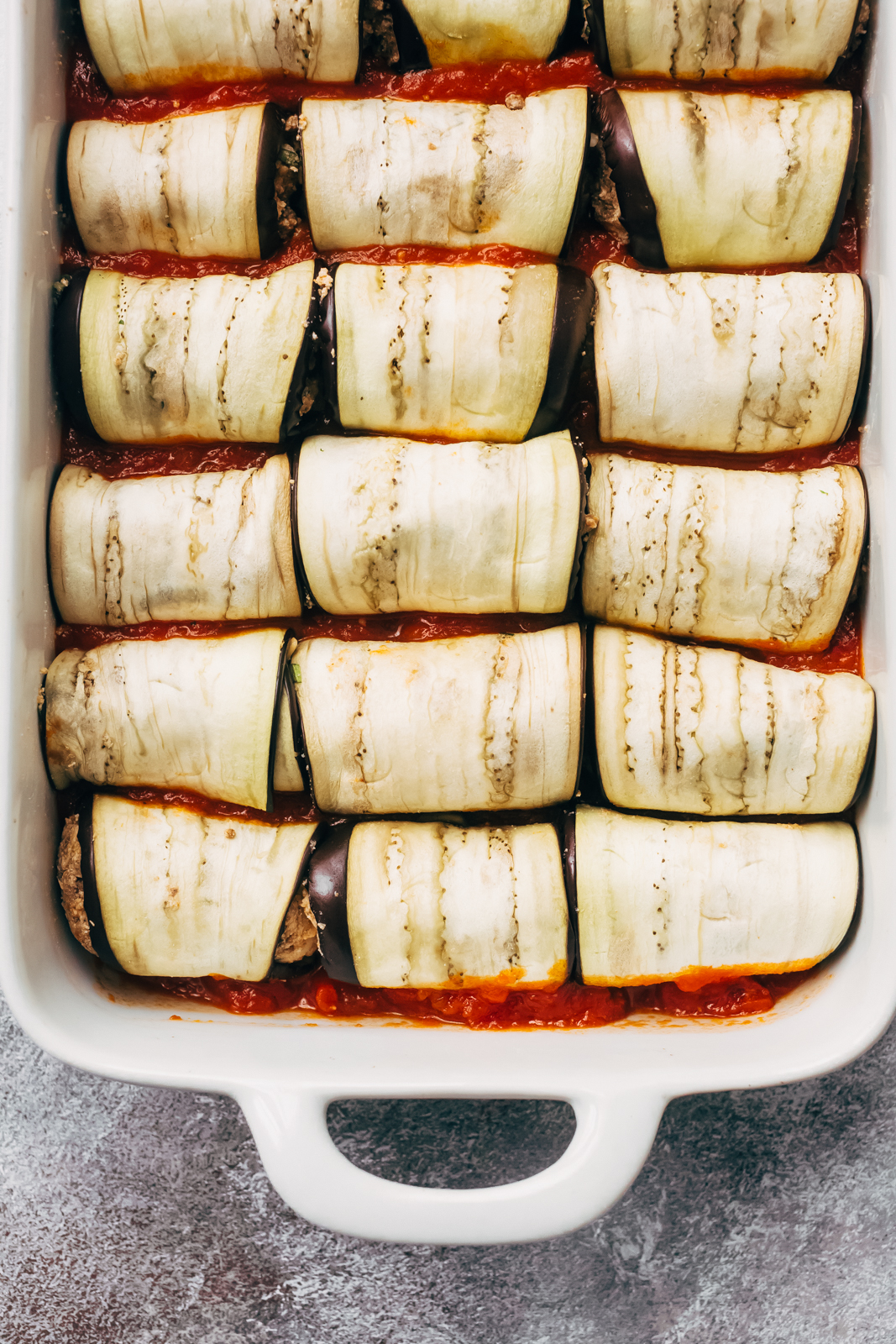 eggplant rolled with meat mixture in rows in white baking dish