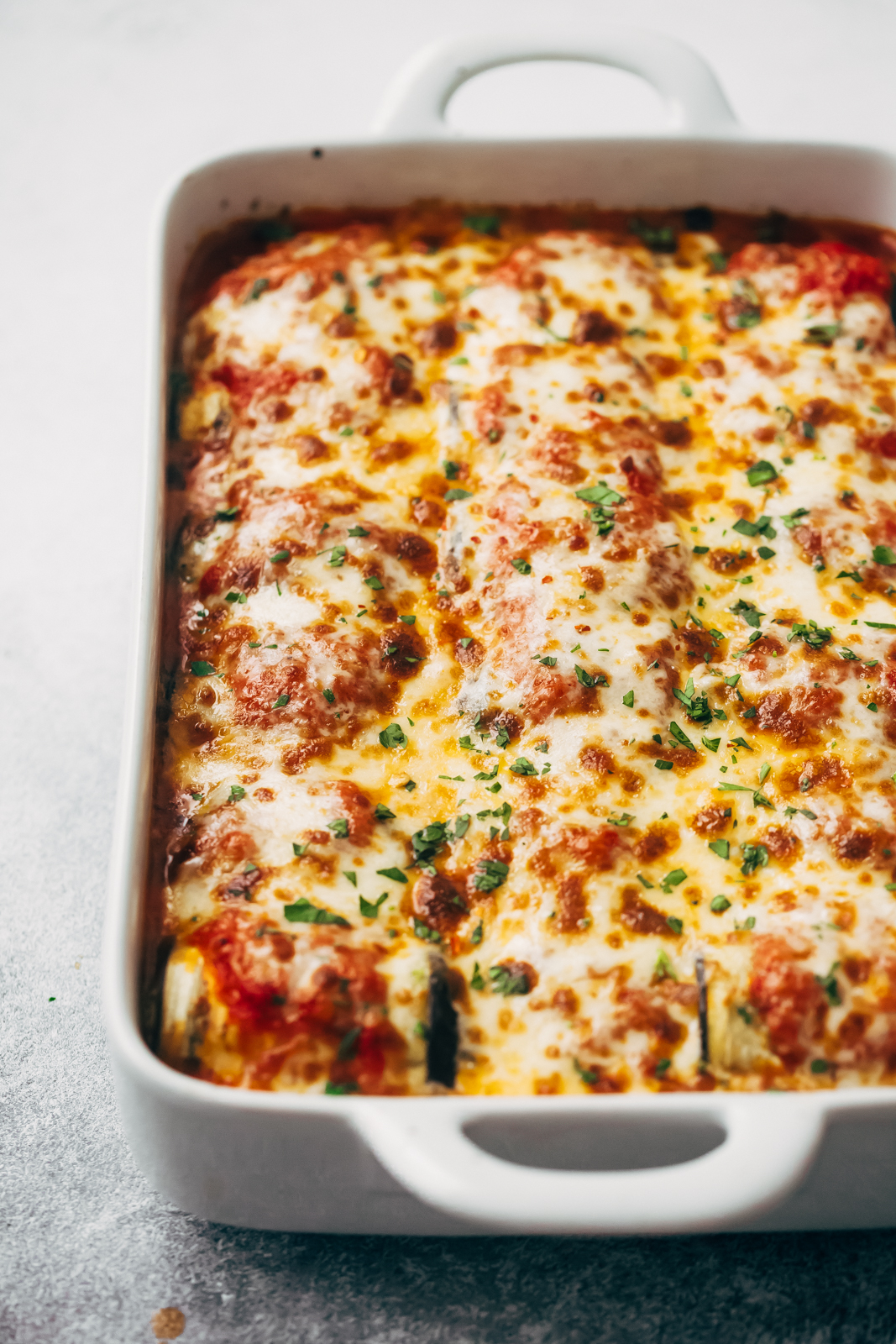 Baked Eggplant Lasagna Roll Ups with melted cheese in white baking dish