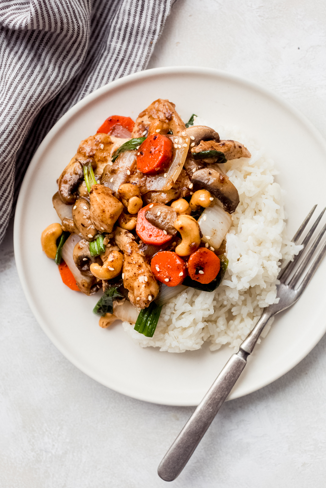 white plate with jasmine rice, fork, and prepared cashew chicken