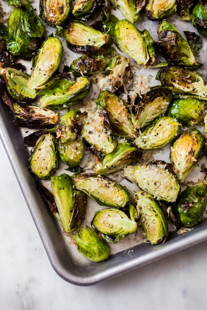 brussels sprouts topped with pecorino cheese on baking sheet